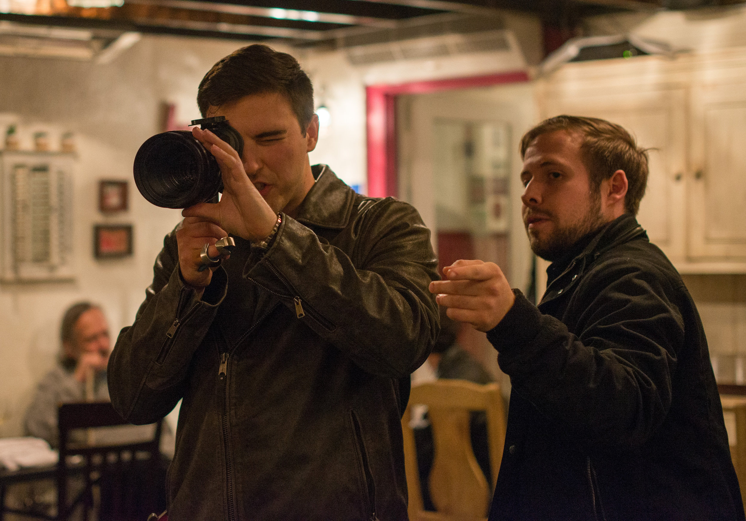 Director Brian White speaking with Director of Photography Cooper Ulrich setting up the restaurant shot on the viewfinder.