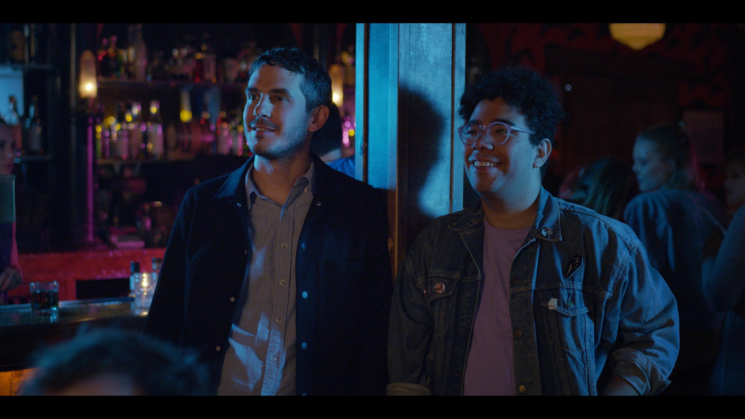Bill (Tate Ellington) and Manny (Oscar Montoya) watch Jackie Tohn perform