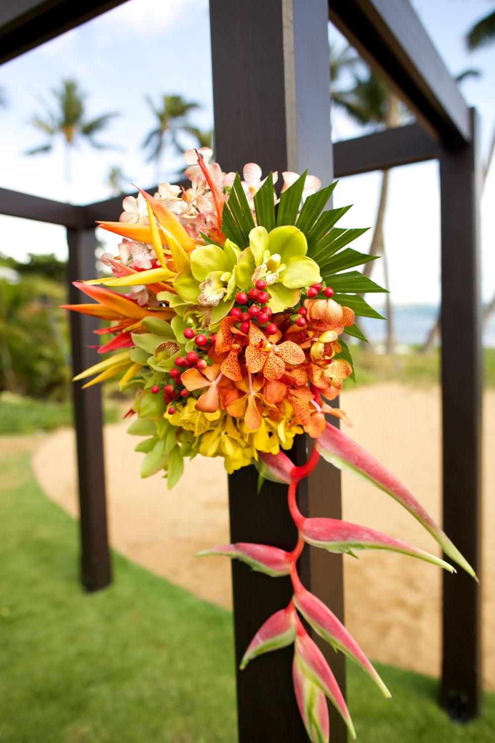 Bright tropical wedding ceremony arch by Bliss Wedding Design - photo by Anna Kim Photography