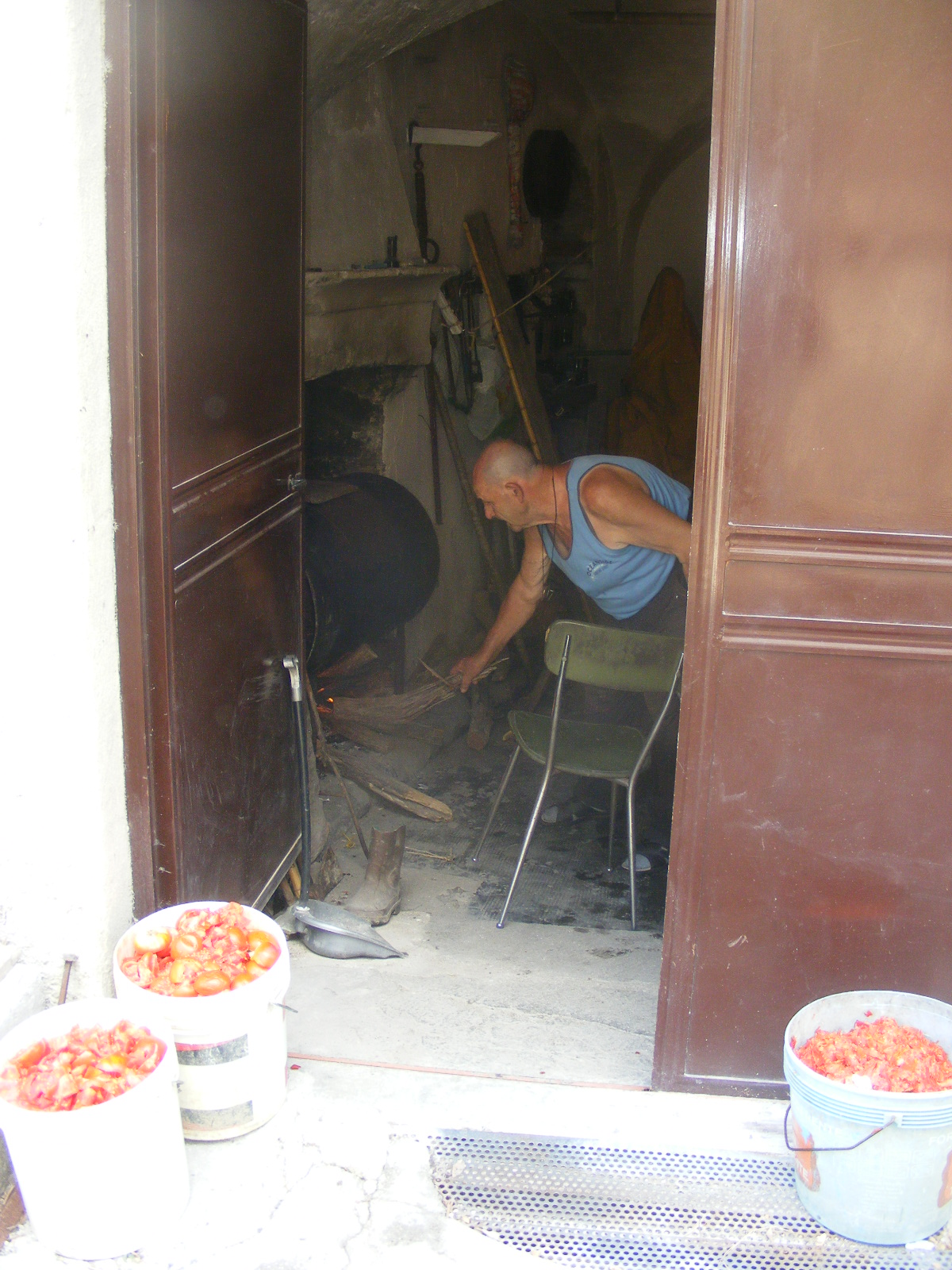 Antonio stewing tomatoes in an old oil barrel in his garage. Poor tomatoes.