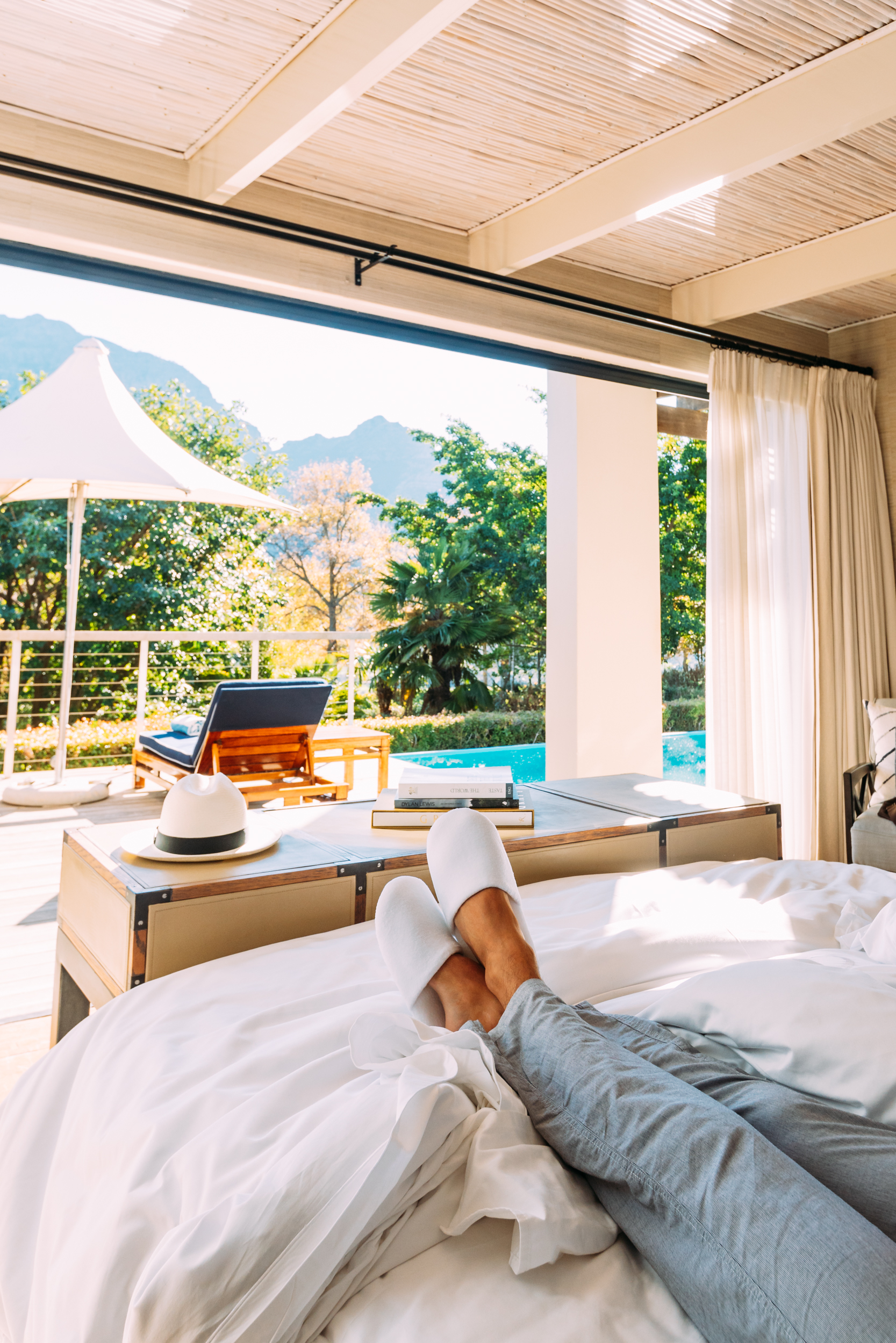 A man with his feet up in bed with plush slippers enjoying the view from the Presidential Lodge at Delaire Graff Lodges & Spa
