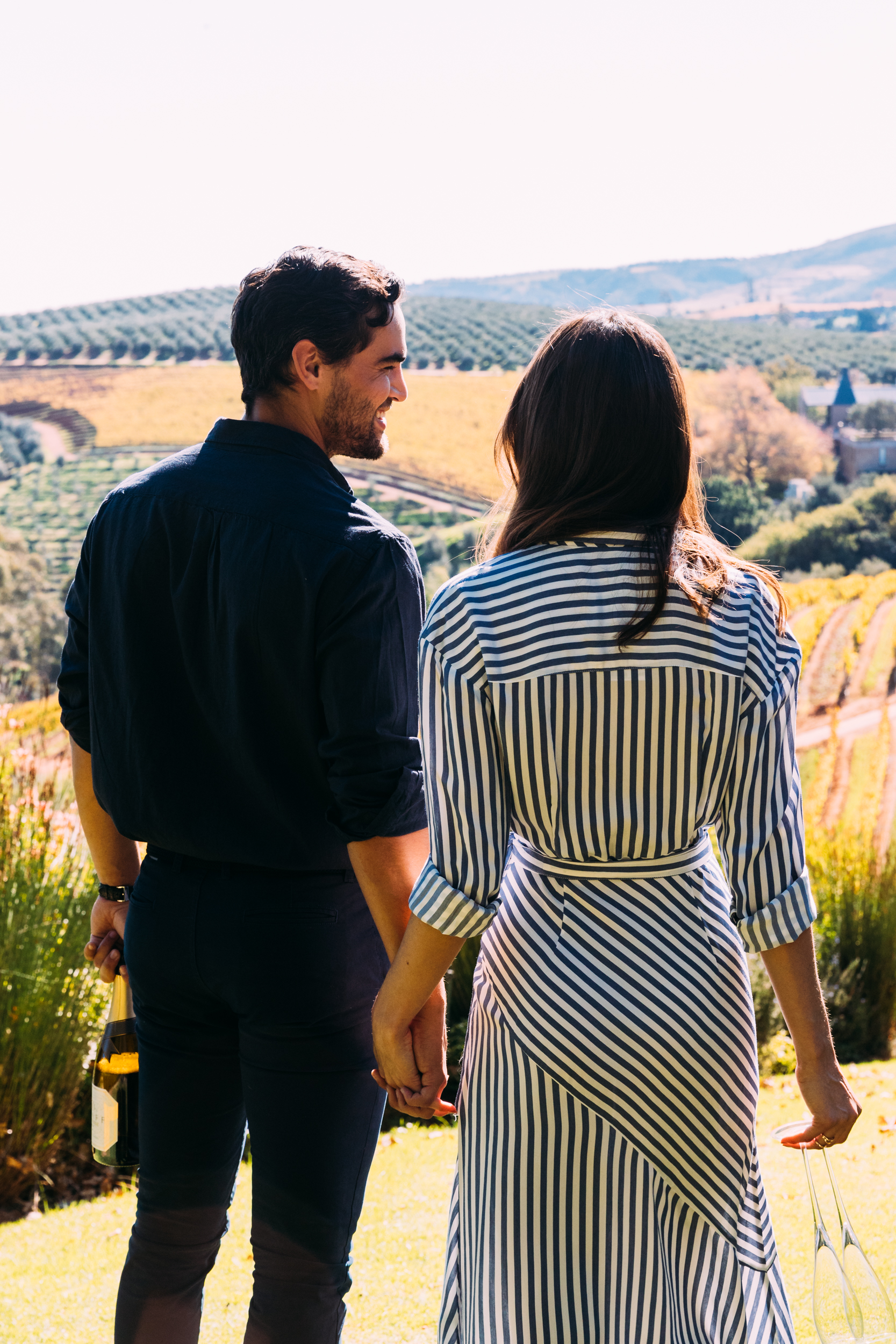 A couple are walking through the landscaped garden admiring the view of the Delaire Graff Estate vineyards