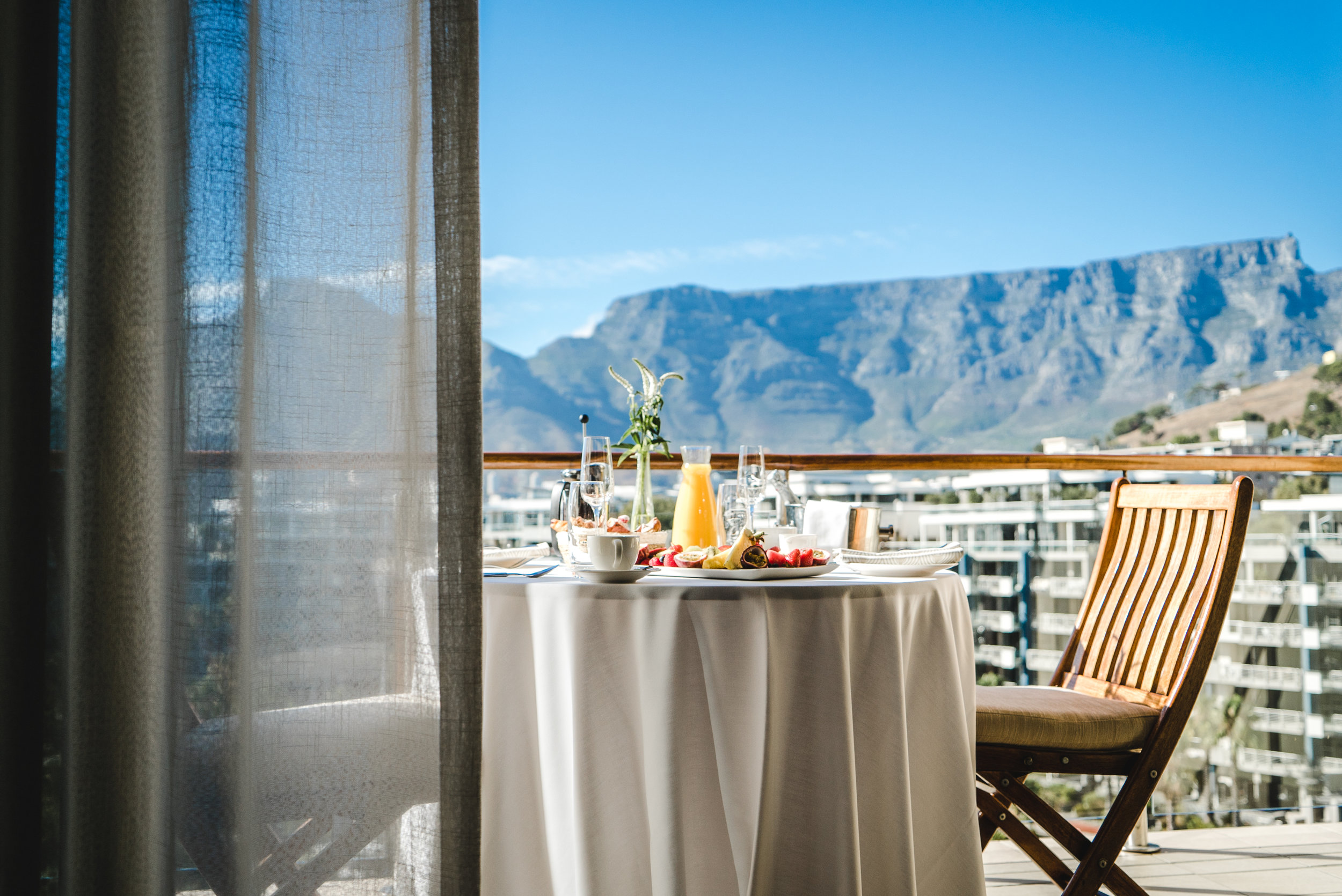 A continental breakfast set on the balcony at the One&Only Cape Town with a beautiful view of Table Mountain