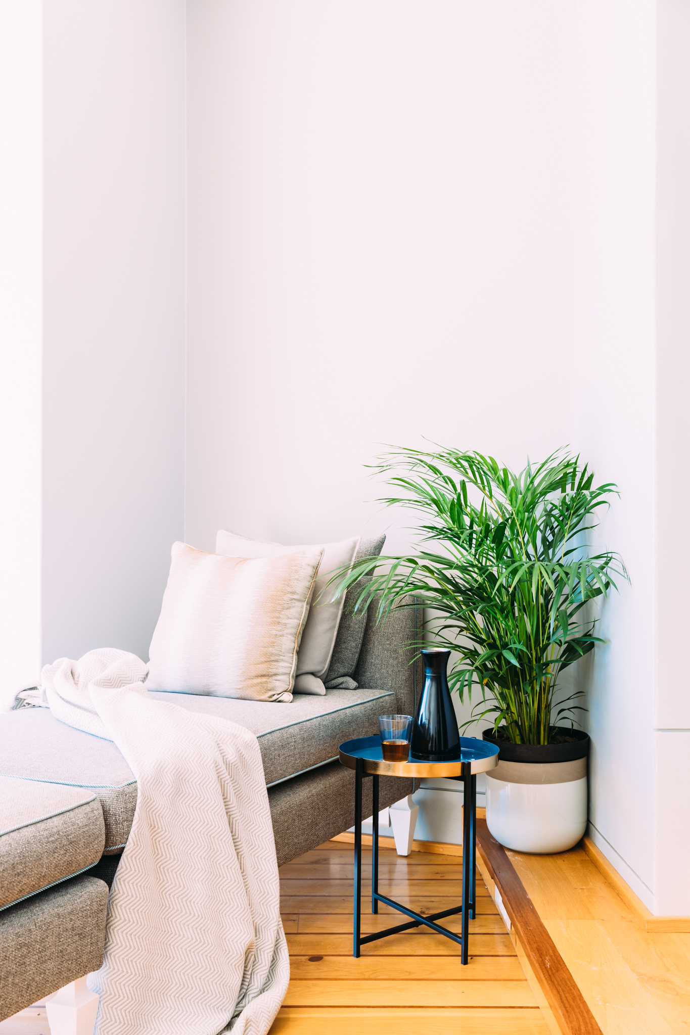 A grey lounger with a throw draped over it with refreshments on a side table and large indoor plant in the Ellerman House Spa lounge