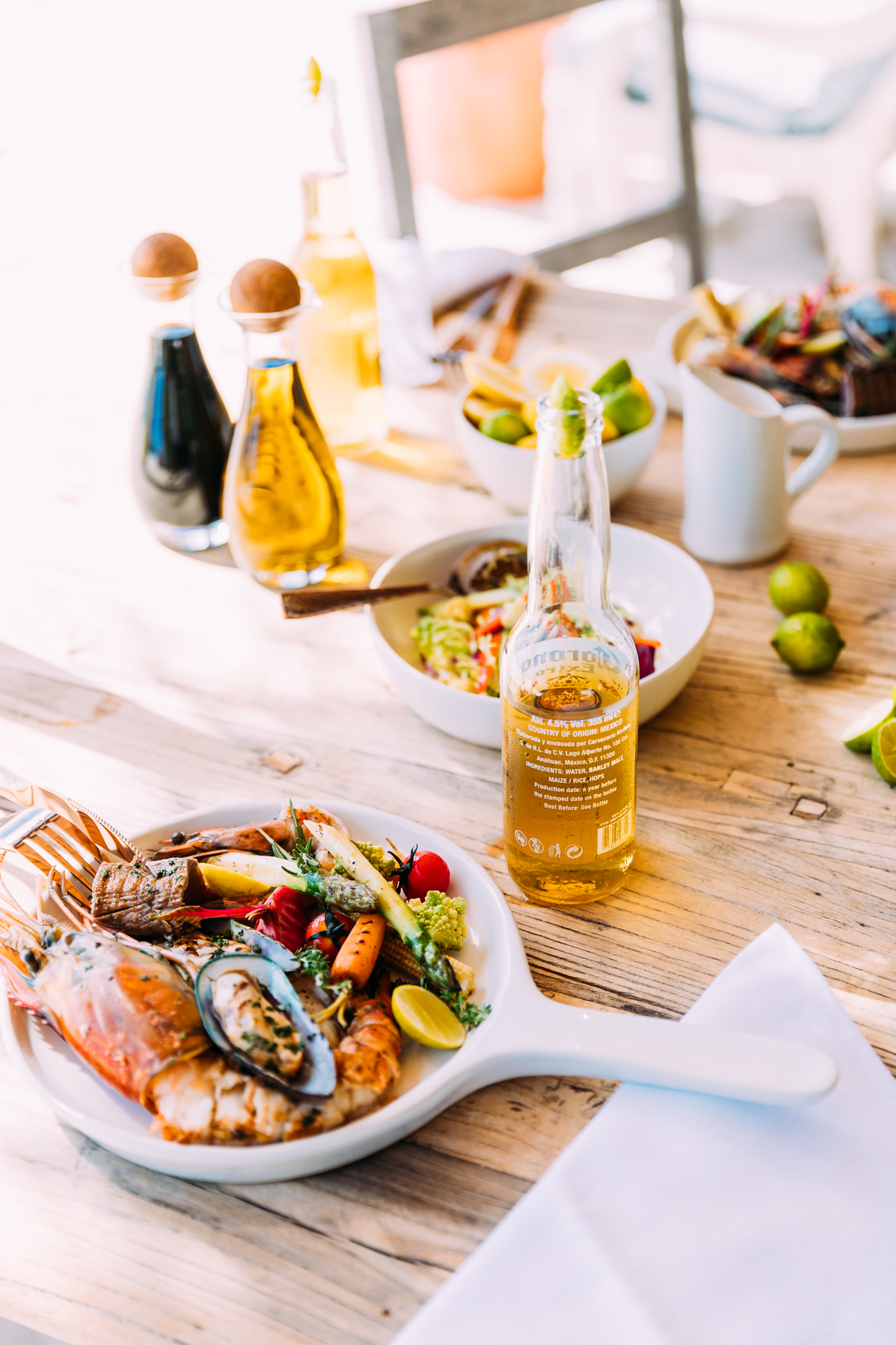 A seafood lunch of barbecued lobster, prawns, mussels and grilled vegetables paired with ice-cold Coronas at West Beach Bar on North Island in Seychelles