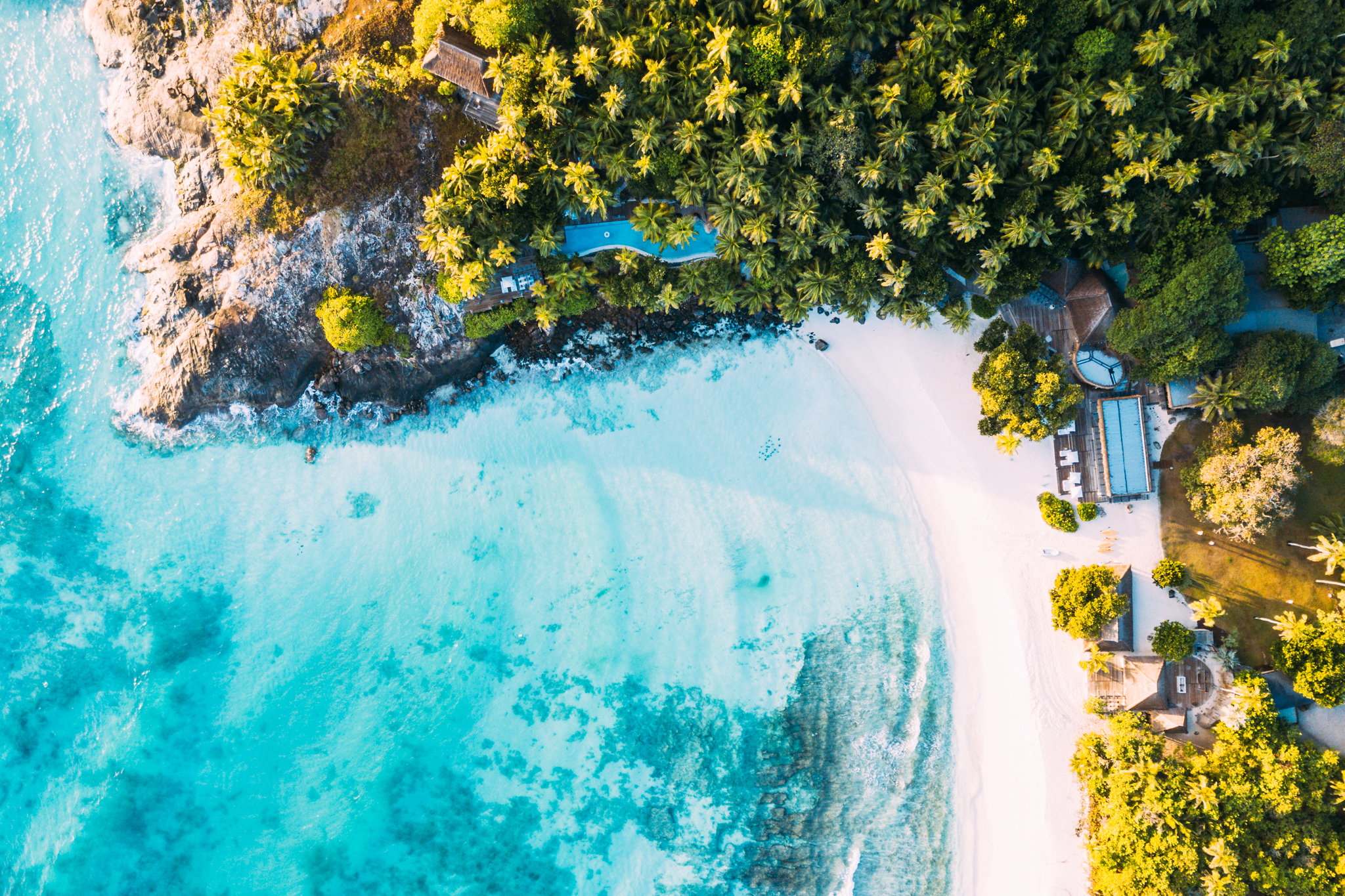 A tropical island aerial of the bay of East Beach on North Island Seychelles with azure ocean, waving palm trees and soft white sands