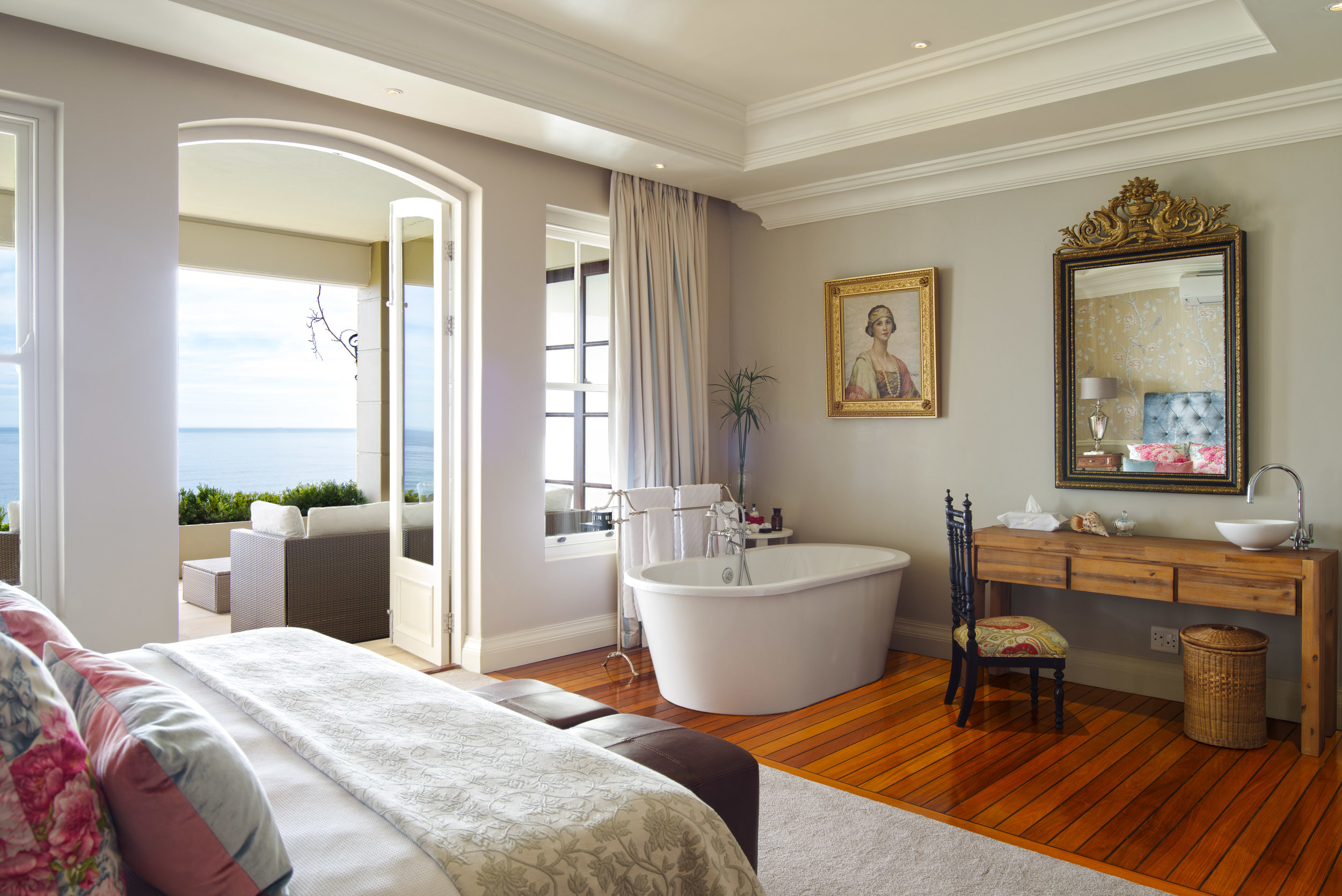 The Queen Suite at 21 Nettleton with a plush bed and feature bath in the bedroom looking onto the private deck with ocean views