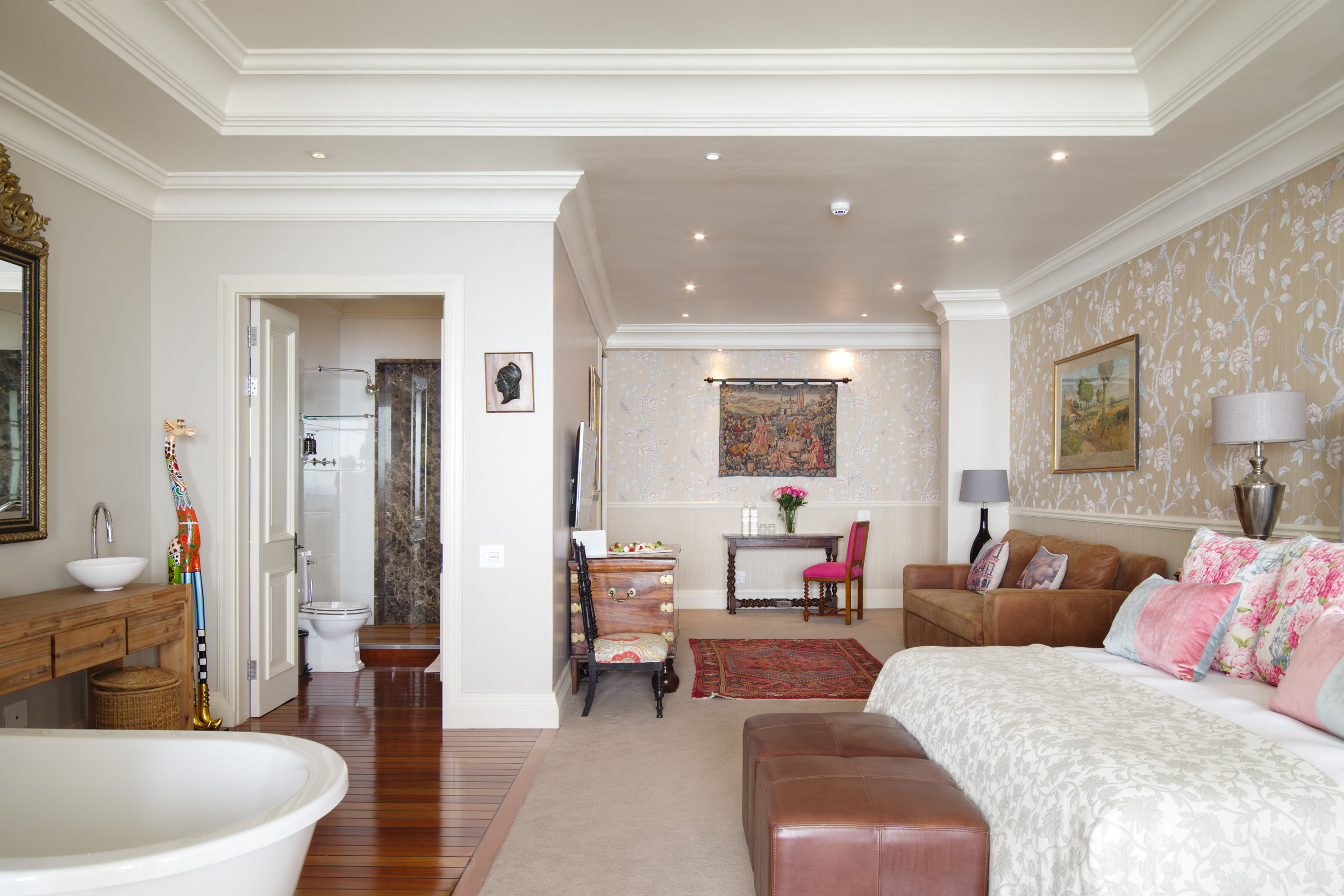 Looking into the Queen Suite at 21Nettleton with a feature bath in the bedroom and separate walk-in shower and WC plus a comfortable sitting area with bespoke art