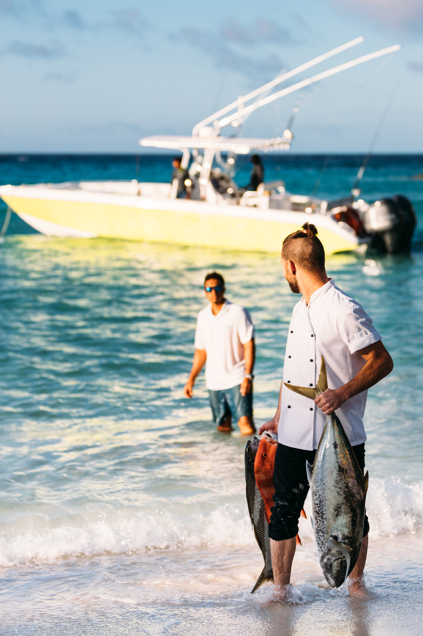 North Island's Executive Chef fetching fresh fish straight from the ocean for dinner off their boat from the Dive Centre Manager in the background