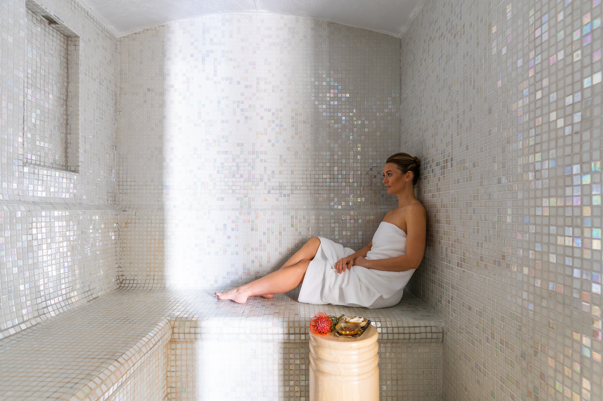 Girl relaxing in the white mosaic Swedish sauna and steam room at Delaire Graff Spa