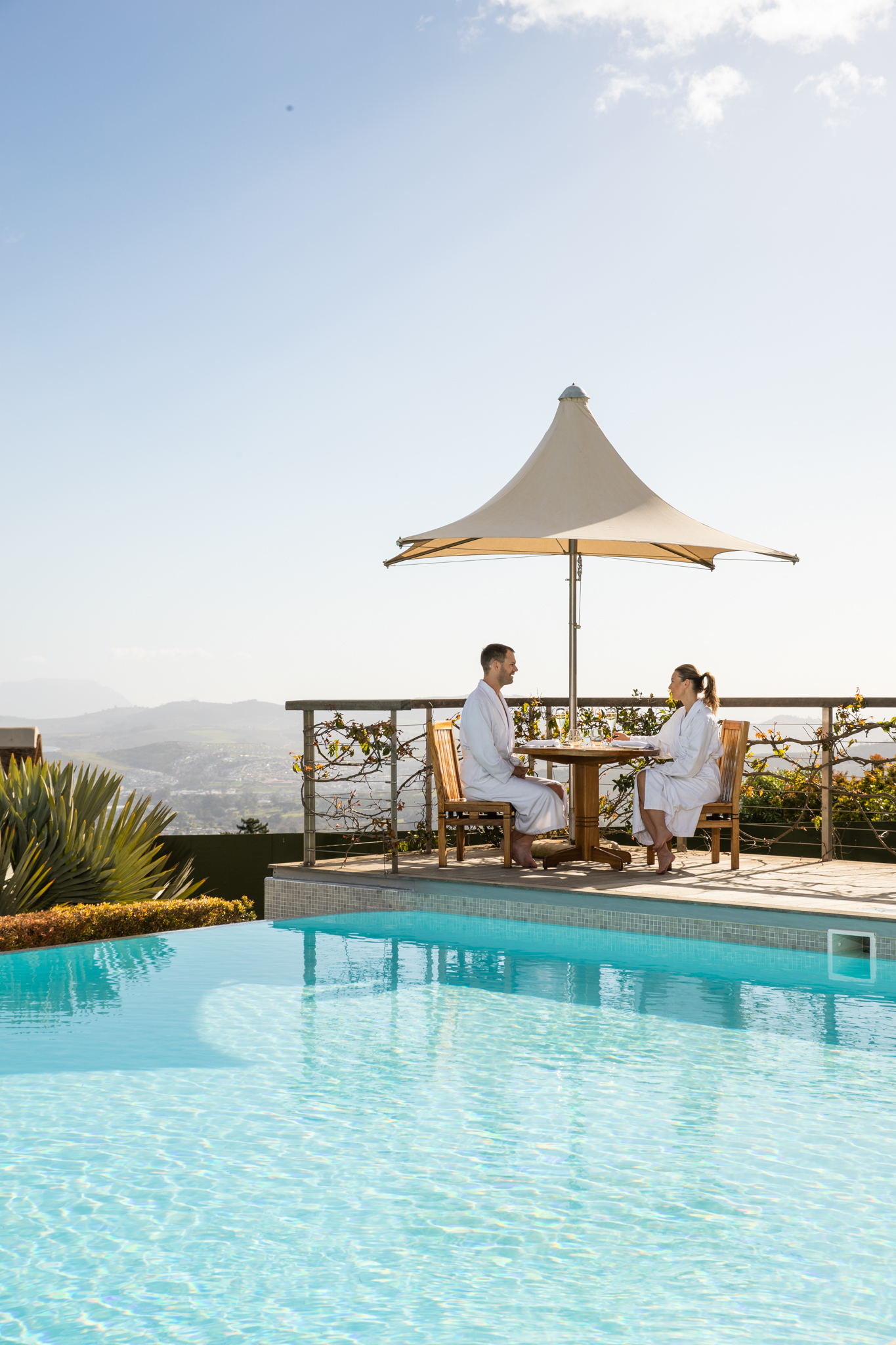 Couple having light lunch on the Delaire Graff Spa deck next to the infinity pool with beautiful views of the Stellenbosch Valley