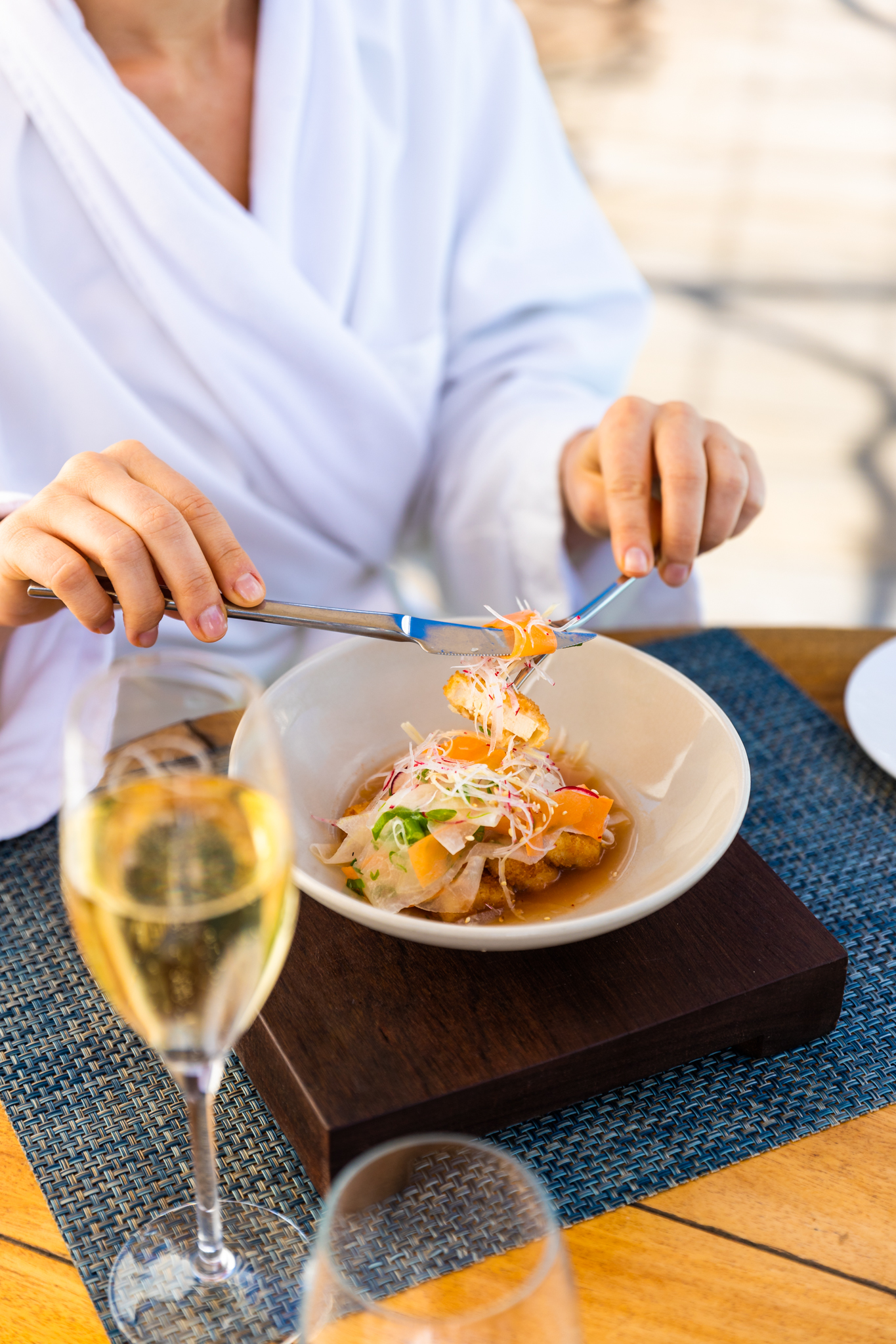 Girl enjoys a light Asian-influenced dish on the Delaire Graff Spa deck menu with a chilled glass of wine