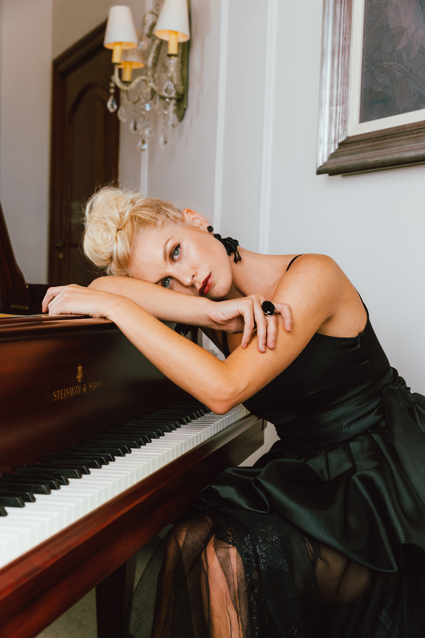 Girl sitting at piano in black Kluk CGDT dress at Ellerman House