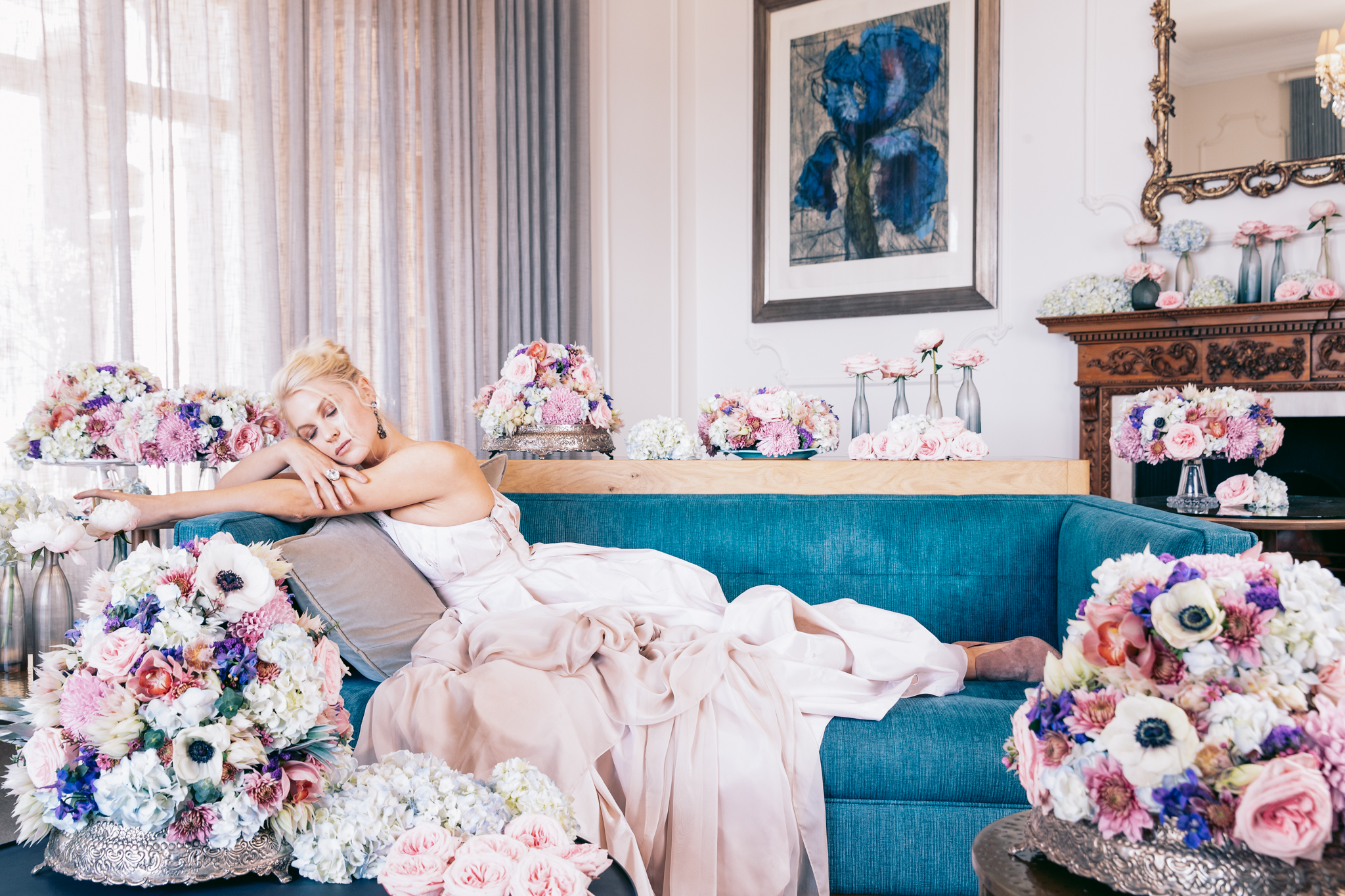 Girl lying on couch in pale pink KluK CGDT dress with champagne in hand surrounded by flowers at Ellerman House