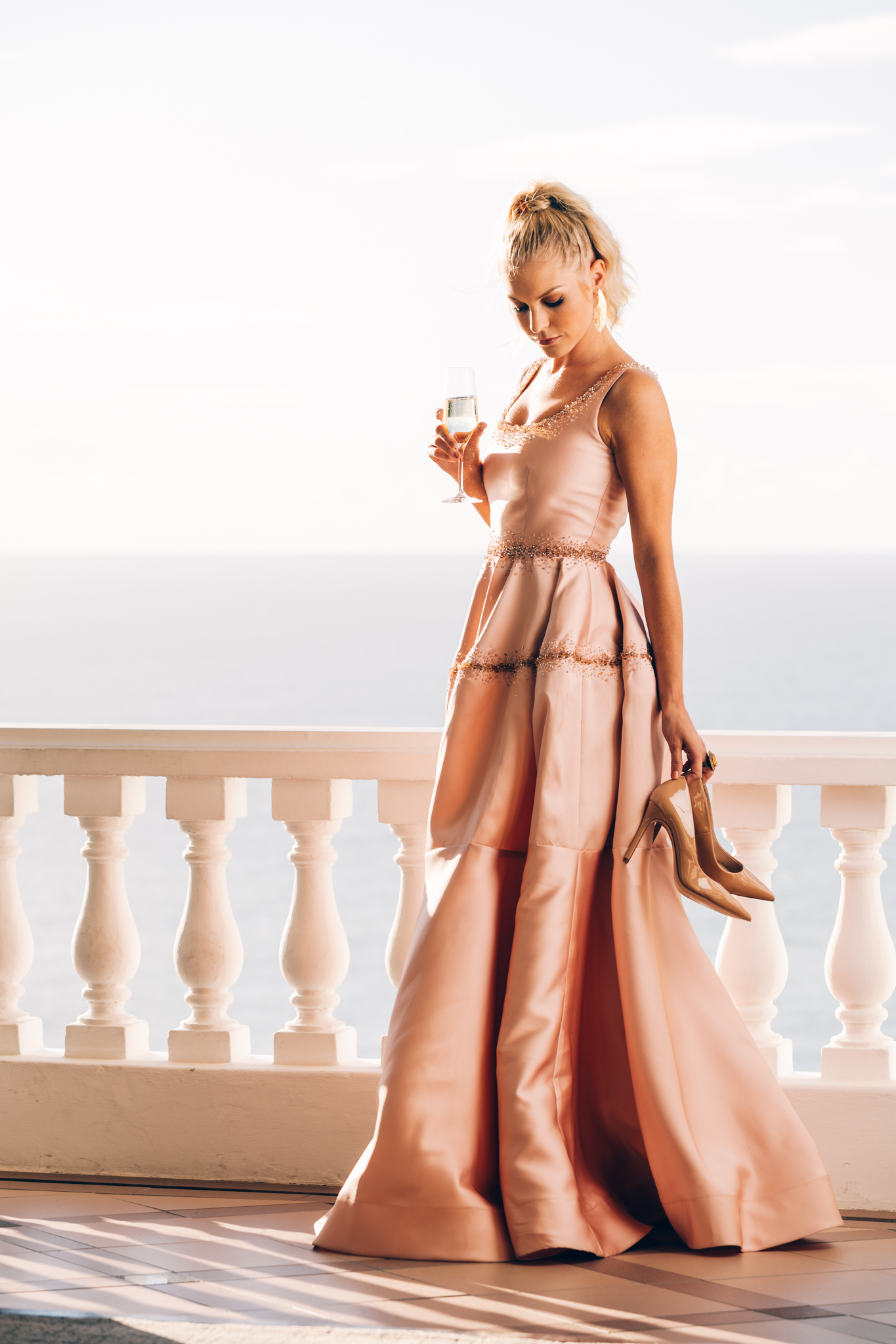 Girl drinking champagne on the balcony at Ellerman House dressed in pale pink Gavin Rajah dress with Steve Madden shoes in hand