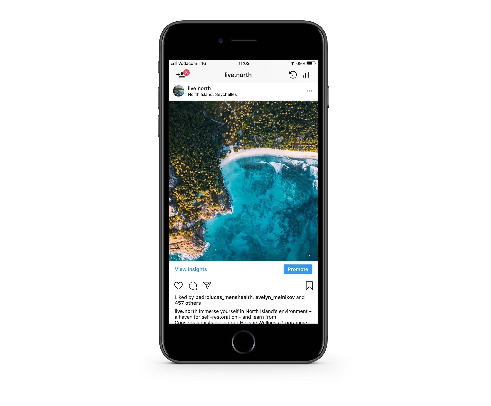 A iPhone showing North Island's instagram post of an aerial of the private island featuring azure waters, emerald palm trees and soft white sands