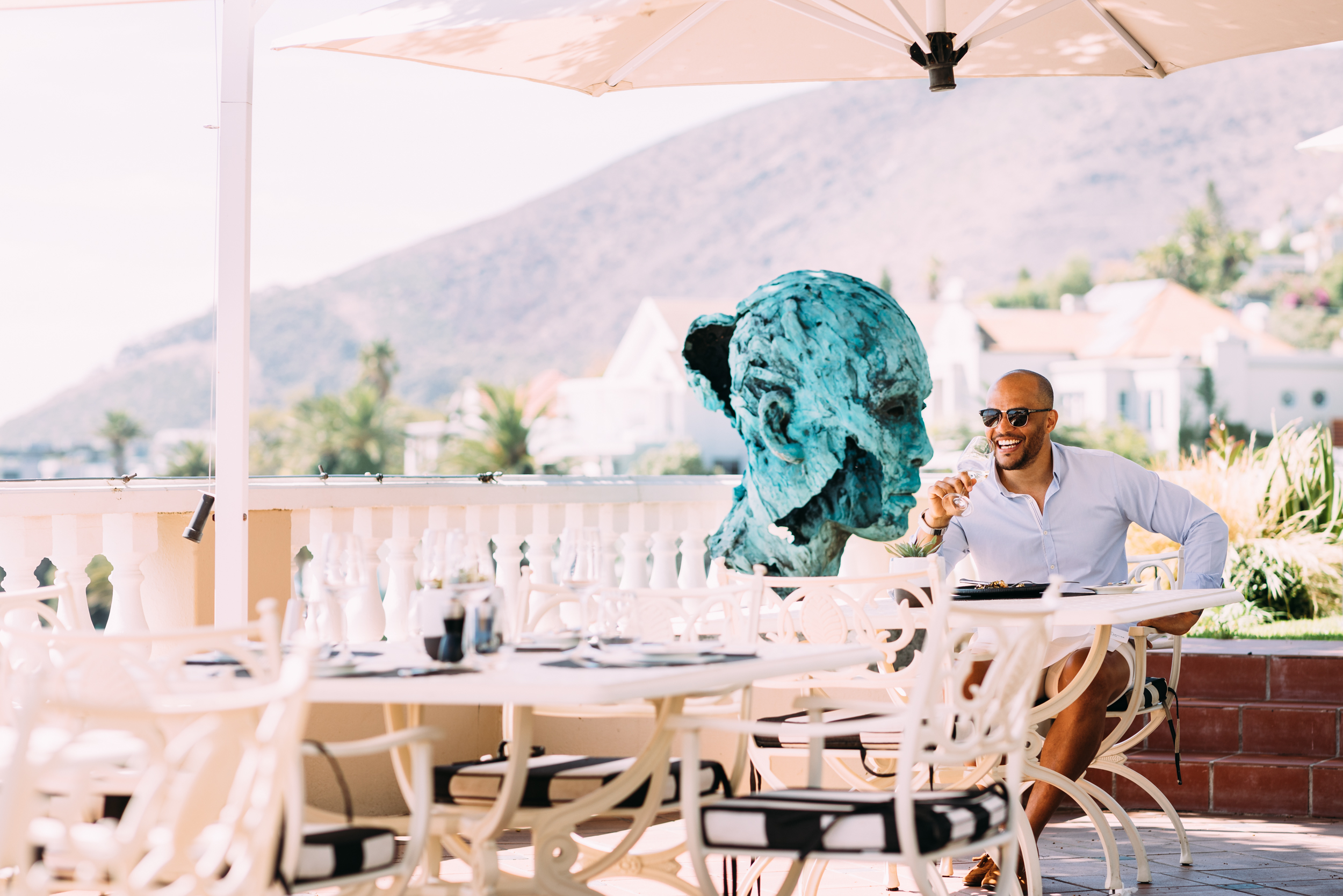 Harry Jameson enjoying lunch at Ellerman House with Lionel Smit sculpture in the background.