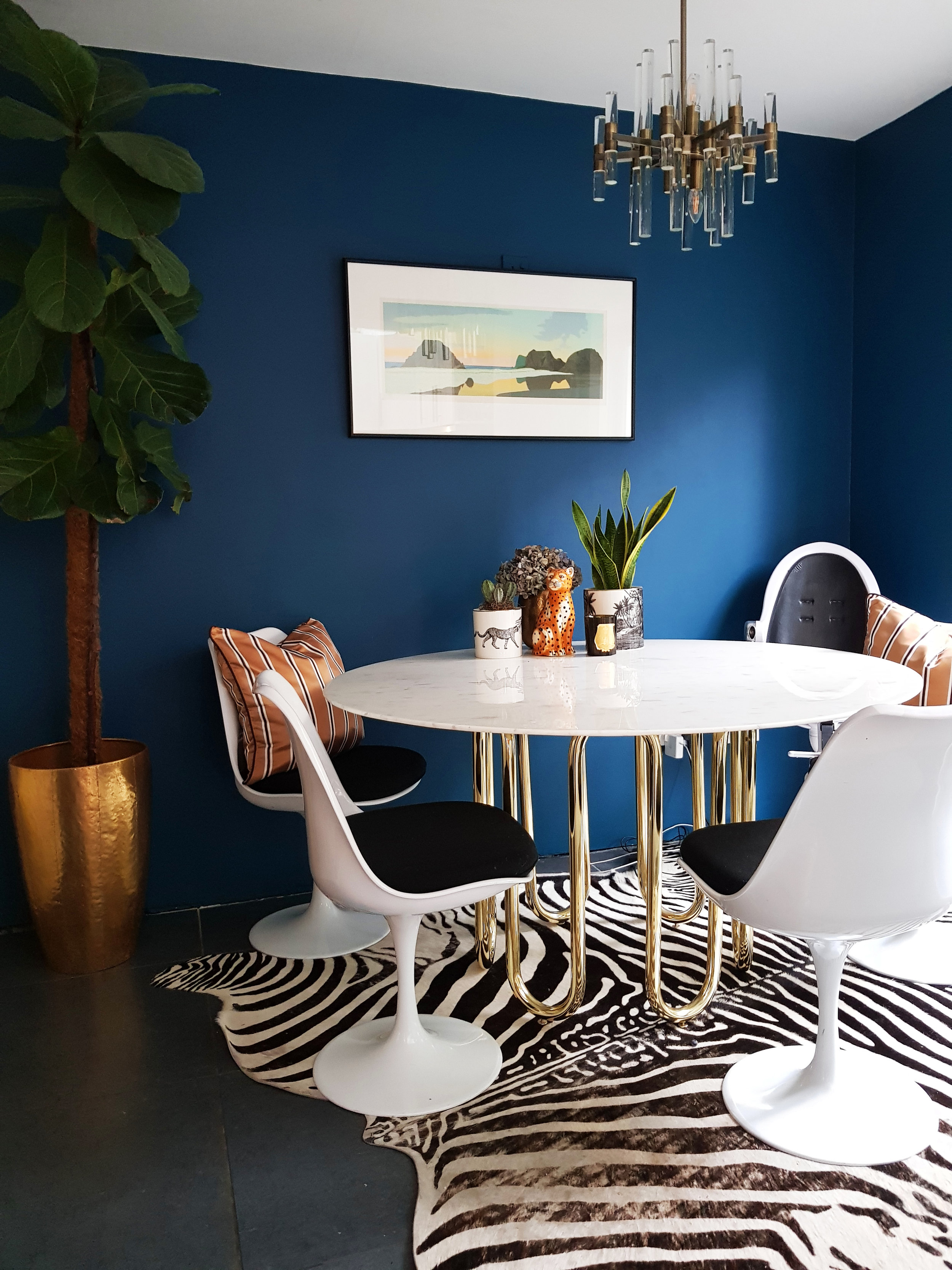 In the dining room, a  Jonathan Adler  Scalinatella dining table in Carrera marble and brass is paired with Eero Saarinen Tulip chairs with Danish wool seat.
