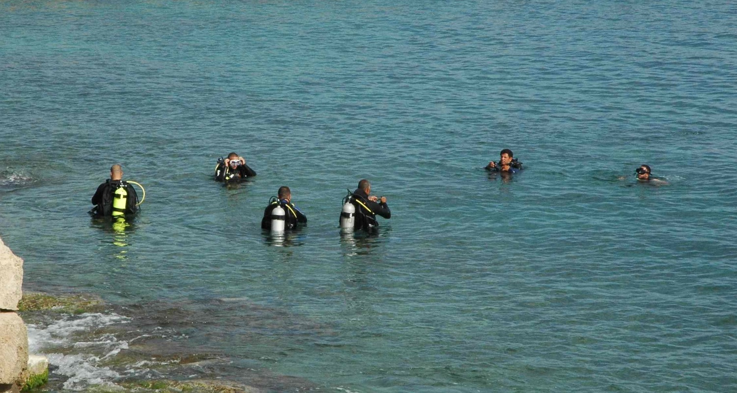 Divers prepare to descend to the remains of the Roman harbor at Caesarea Maritima, Israel.