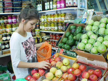 Tamara, a regular customer and a longtime friend of the Samman family, examines the apples.