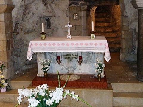 The modern altar in the cave. Note the black letters between and candles and below the altarcloth.
