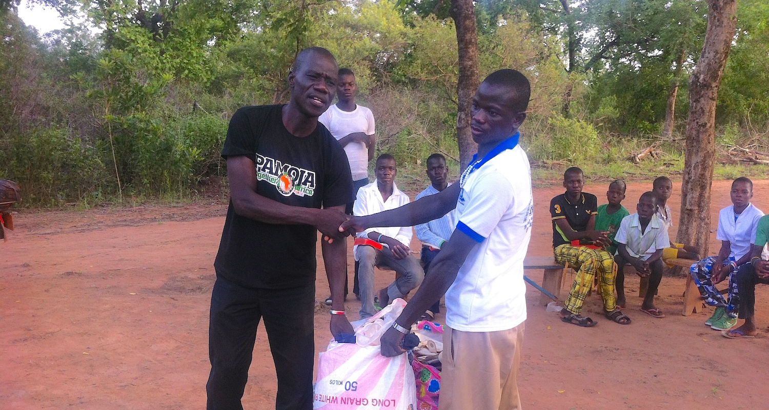 Pastor Philip (on left) helping distribute clothing.
