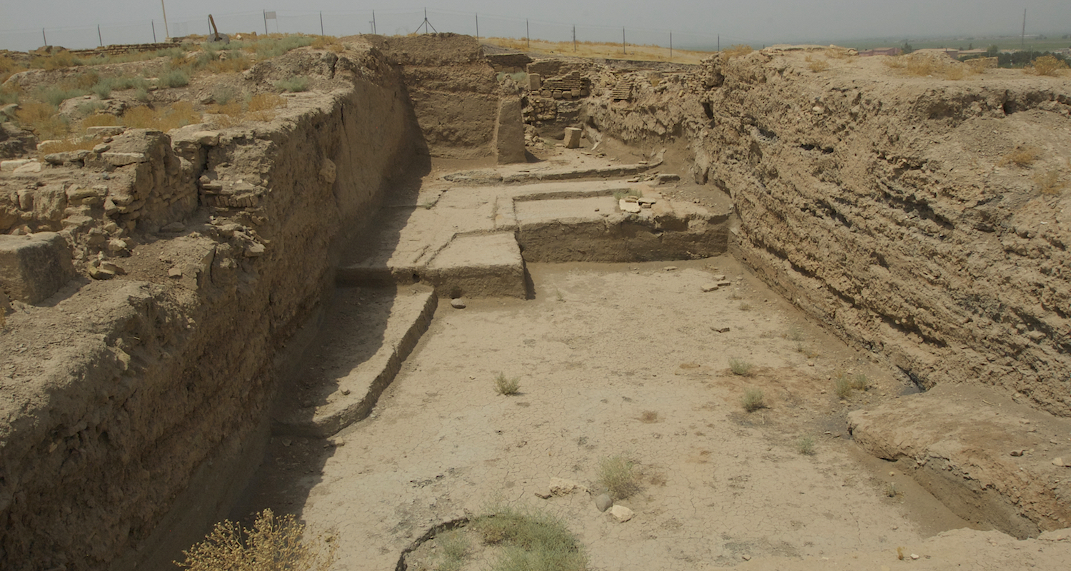 View through a chain-link fence to a recently excavated area of Haran.