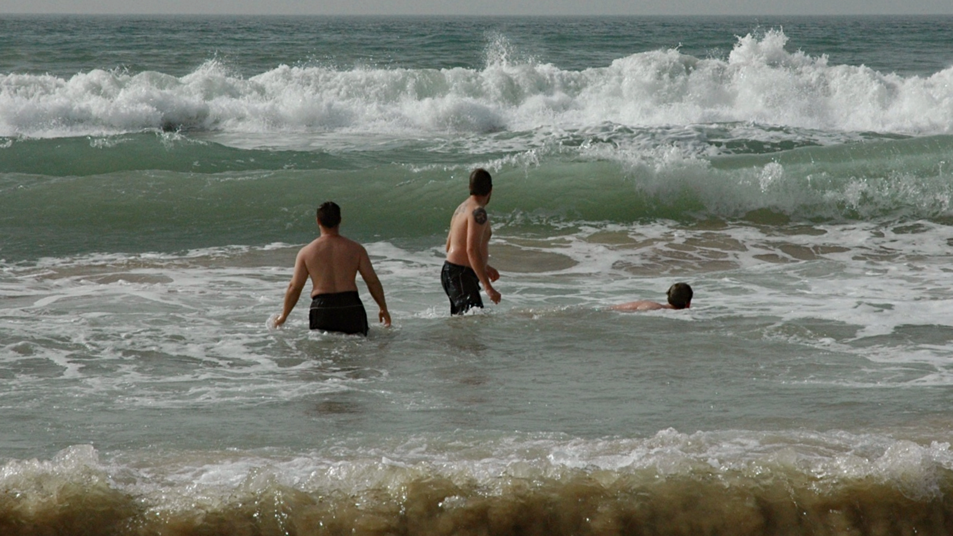 Study-tour students play in the Mediterranean surf.