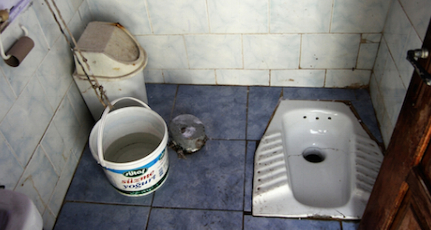 """Nothing underlines this problem as clearly as the ever-popular """"squatty potty"""" or """"Turkish toilet."""" These are widespread in rural and less """"western"""" areas of the Middle East. Performing one's duty at this station requires balance, ingenuity, and the careful manipulation of bottomside covers (i.e., let nothing touch the floor!). Note the empty toilet paper roll on the wall. This is the default position."""