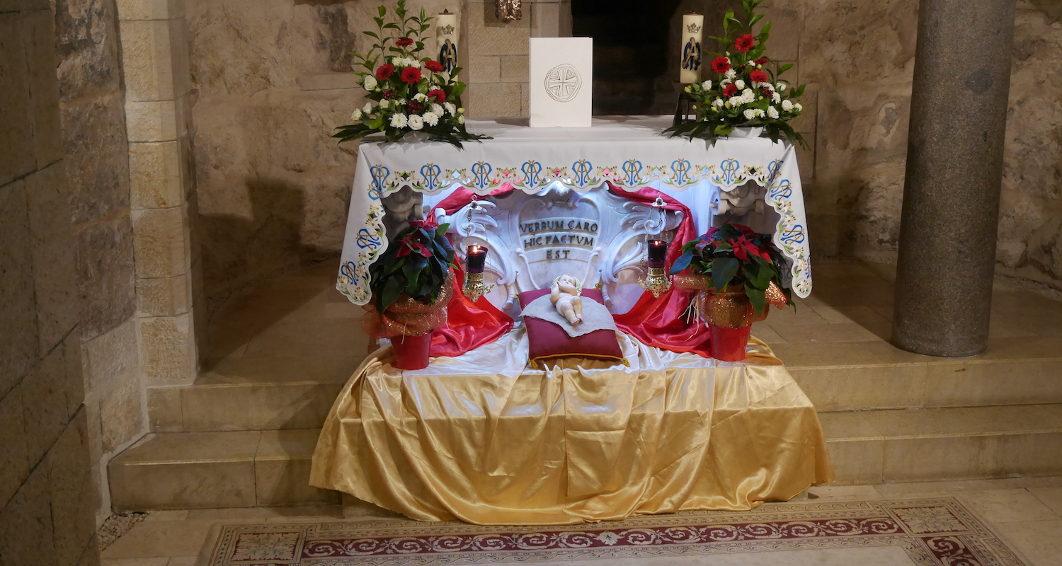 Every church we visited was festively decorated in the colors of the season. Here, at the altar where tradition suggests that Mary received the announcement that she would bear a son, a model of the Christ-child is flanked by colorful poinsettias.