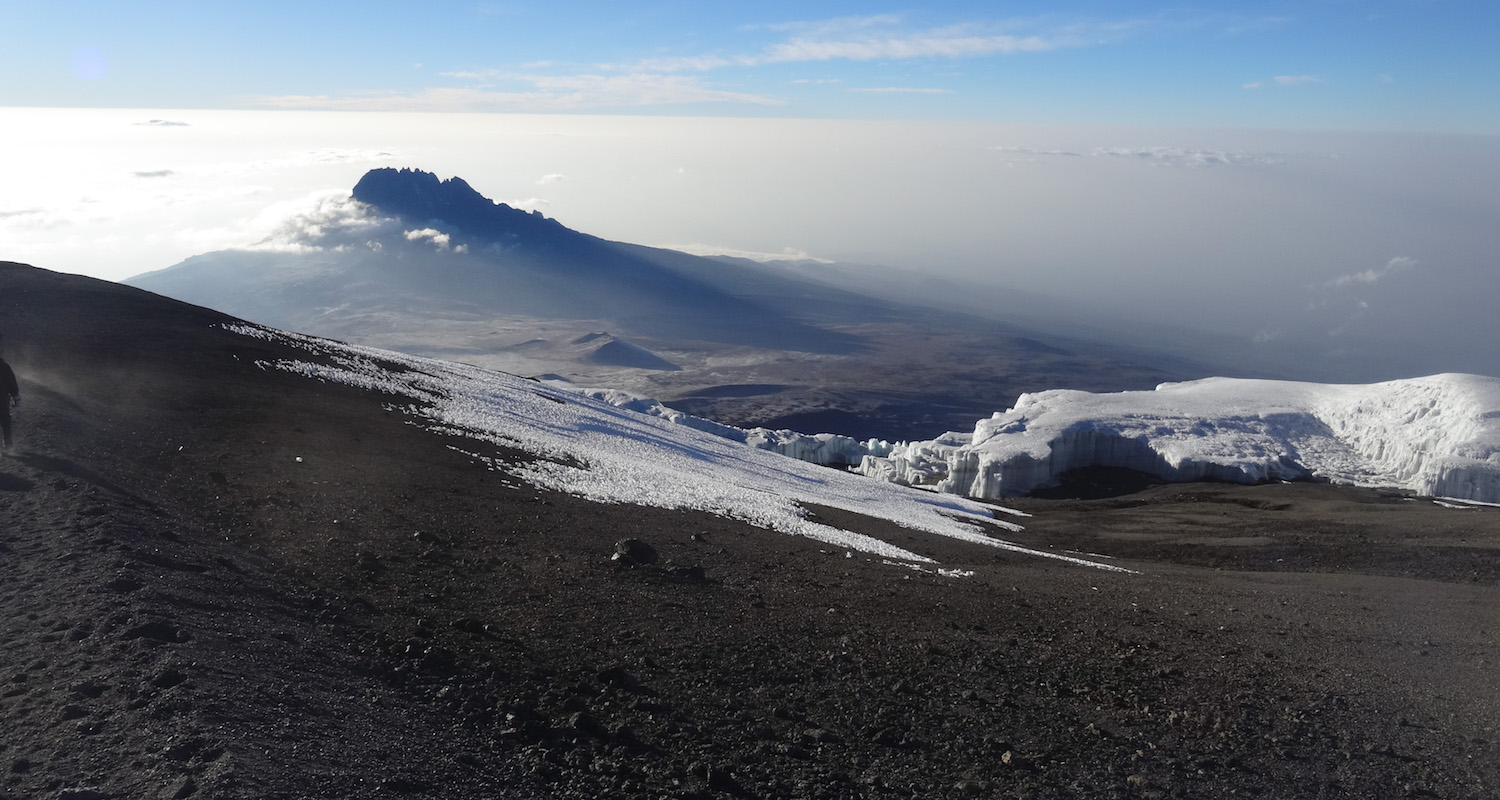 The sunrise illuminates the broken summit of nearby Mawenzi. There are not many places (apart from the window of a jet plane) where you can look    down    upon a peak nearly 17,000' feet high.