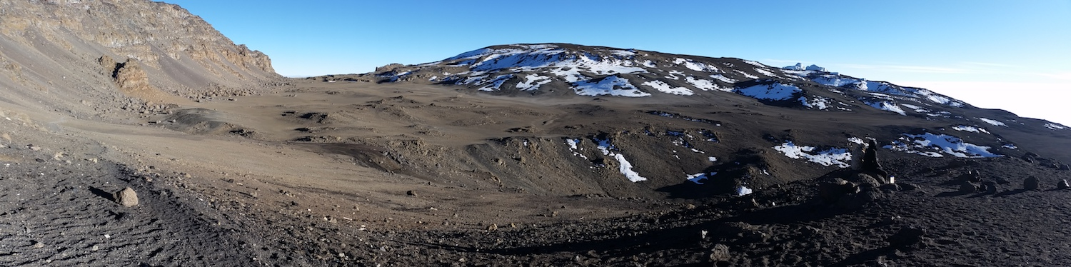 A natural amphitheater. I shot this panorama to Kibo's rolling top on on my descent. Reusch Crater rises with snow patches in the center of the image. The highest point on the mountain is Uhuru Peak, off screen, to the upper left.
