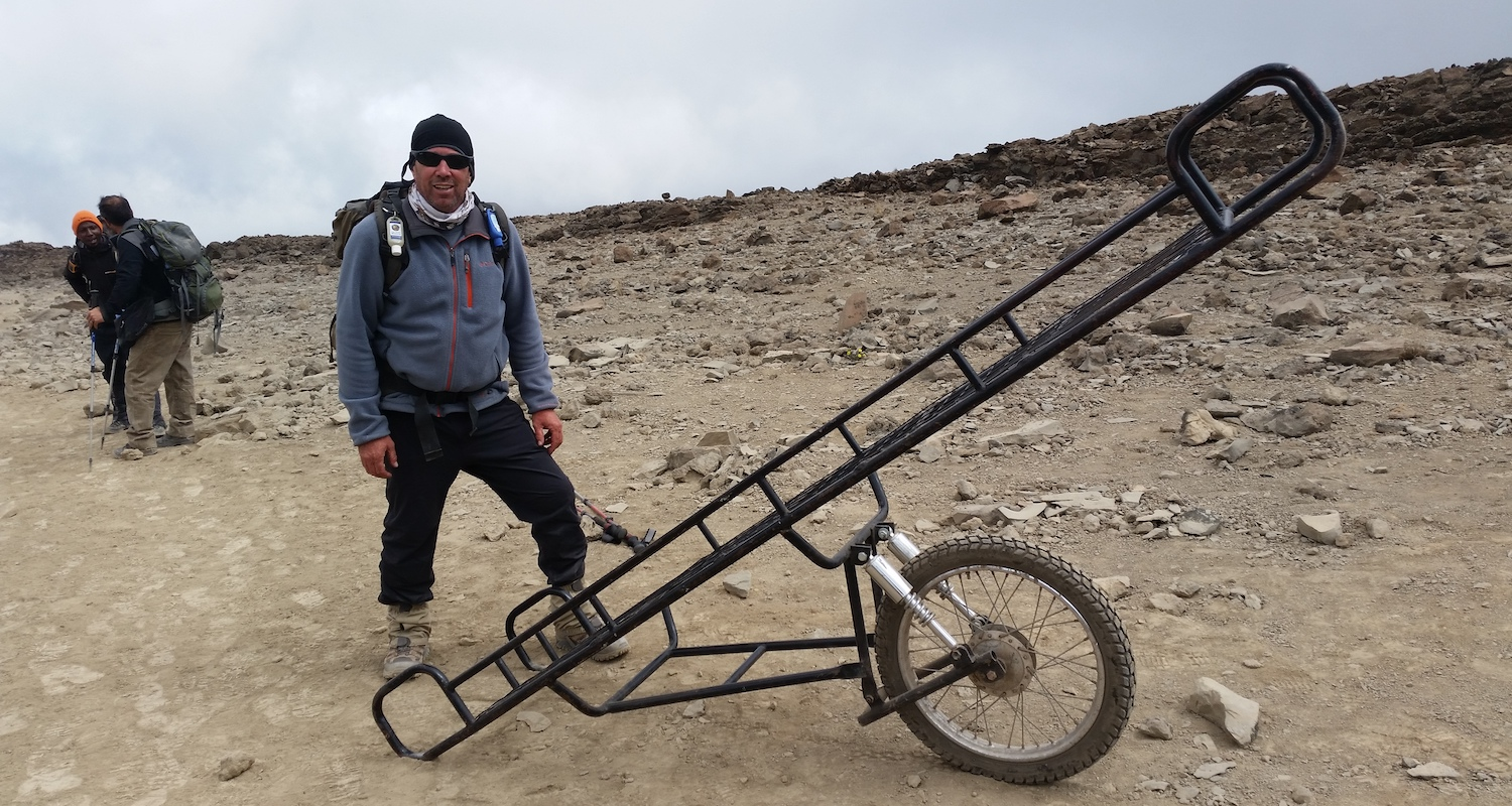 """Tommy stands beside a """"Kili cart"""" This unicycle """"vehicle"""" is used to carry/roll injured climbers over rugged terrain."""