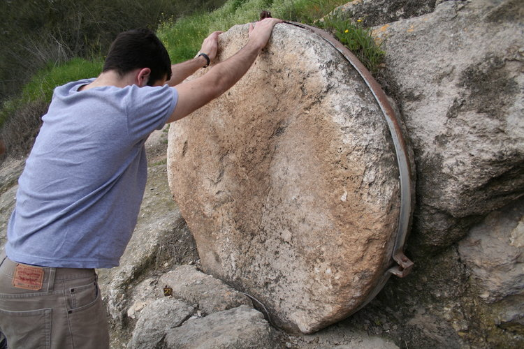 One of our Bible Land Explorer poses for scale. The steel band on this rolling stone should help prevent looters from taking it.