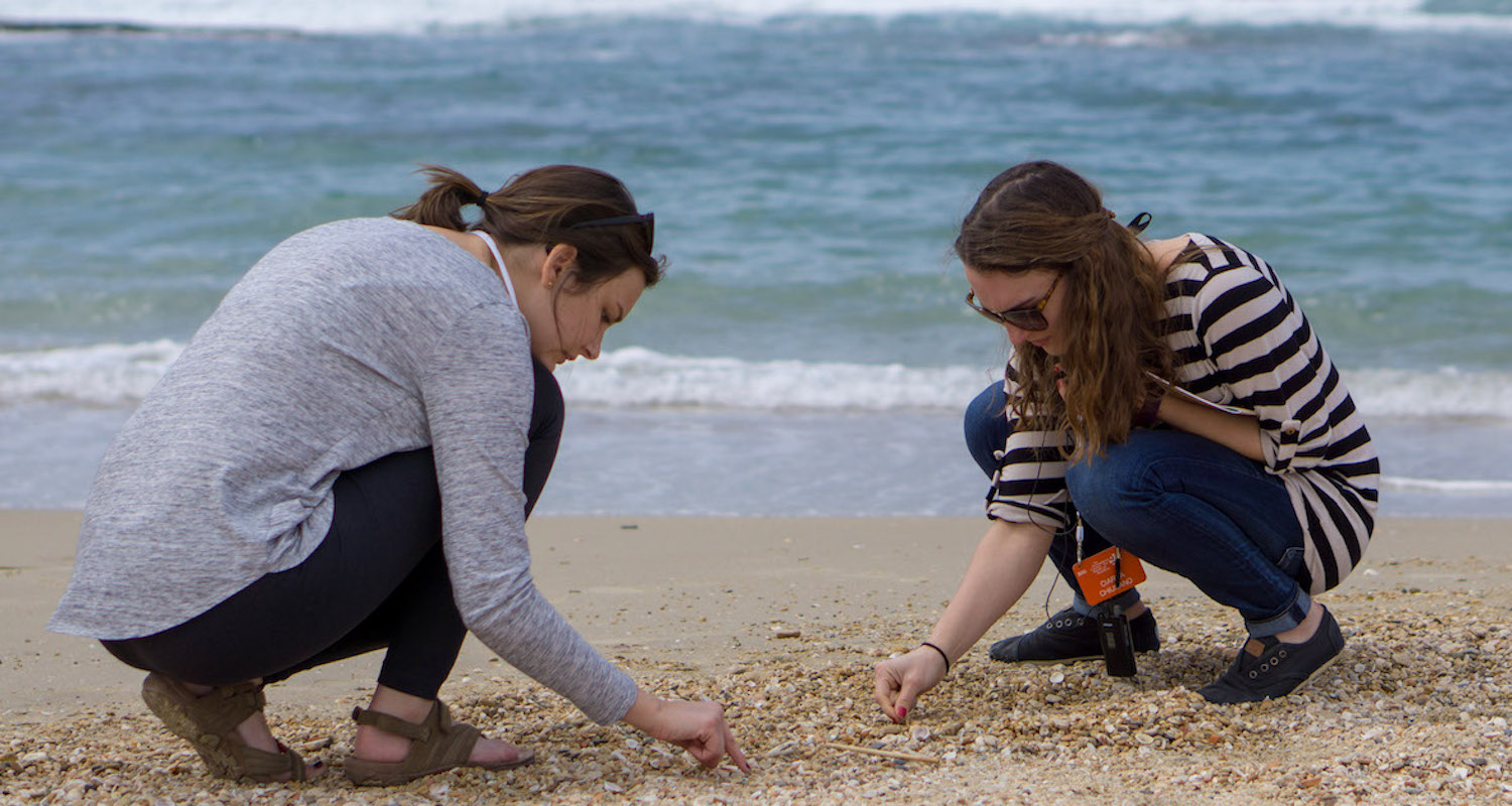 Michaela Wood (L) and Ciarra Chiusano (R)sort through seashells at Caesarea Maritima. The breakers of the Mediterranean Sea roll in softly behind them. Photograph by Bible Land Explorer Adrienne Griffin.