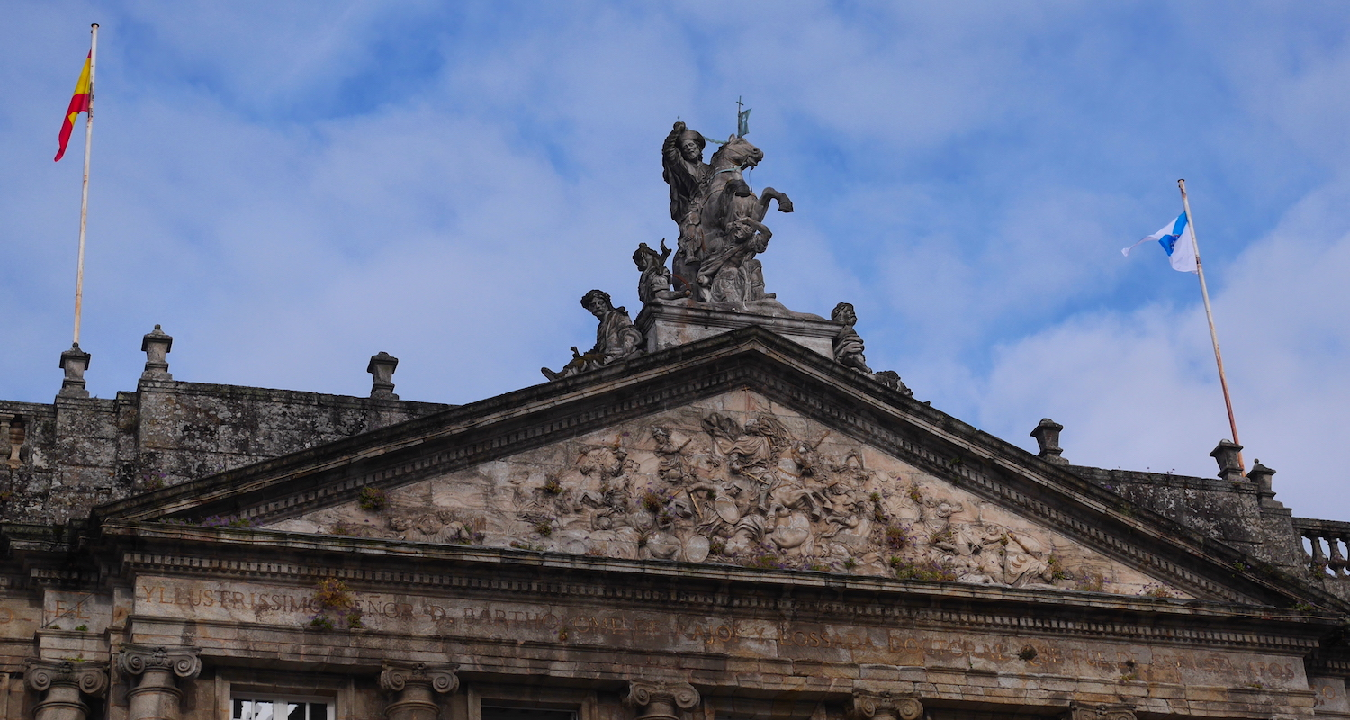 That is Santiago Matamoros riding high above the battle of Clavijo depicted on the pediment of the   Palacio de Rajoy (or Pazo de Raxoi). You can see him glaring down (with sleepy eyes?) at the   Plaza del Obradoiro   in Santiago de Compostela. Once this structure was used in the training of priests. Today it is a government building.