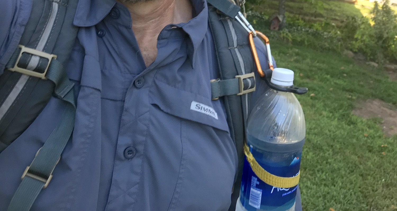The Bottle Bandit makes it possible to clip a disposable water bottle to the shoulder strap of a backpack. The Bandit is made of black silicone. It fits tightly around the bottle neck just under the cap. The hack was the elastic band (yellow in color here) that held the bottle securely against my body.