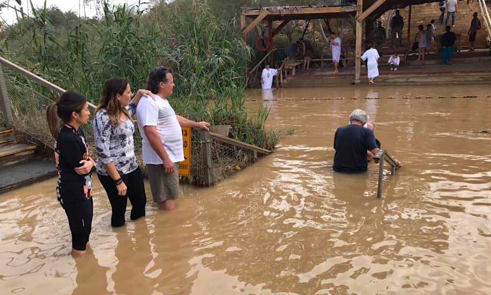 Baptism in the Jordan River. The folk going into the water on left hand side of the photograph are in Israel-Palestine. The folk on the far bank are in the country of Jordan. Here at Qasr Yehud they meet. Image by Amy.
