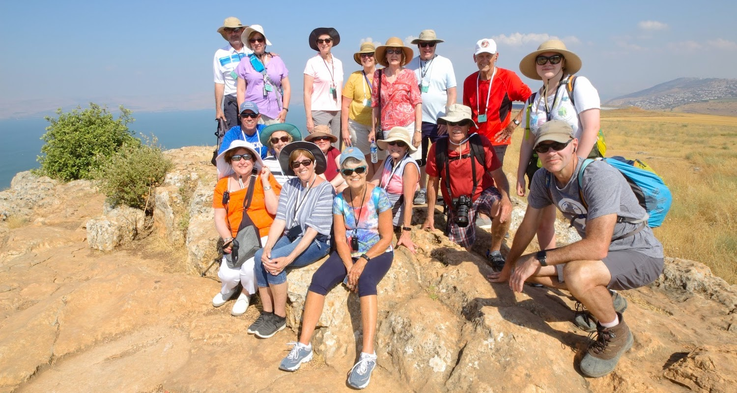 Group photo from the summit of Mt Arbel. The Sea of Galilee shimmers in the distance.