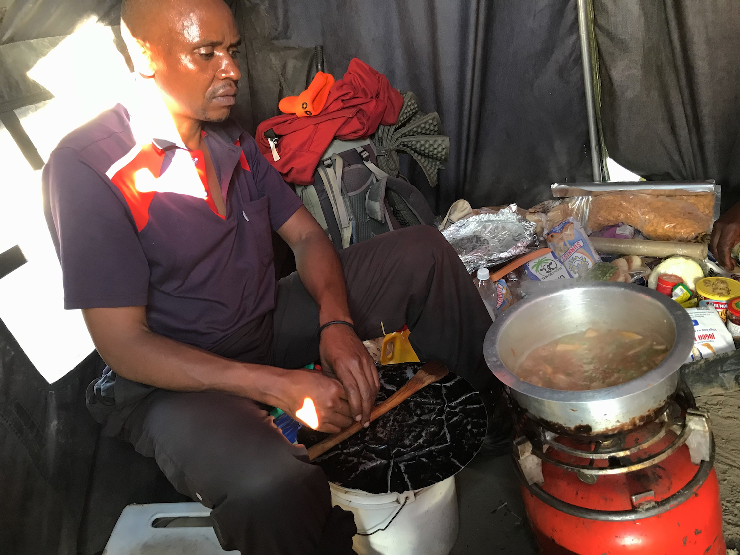 Chef Julius gives me a dinner preview. All meals are prepared on this propane stove. At night, the dirt-floored mess tent converts to sleeping space for Julius and several of the porters.