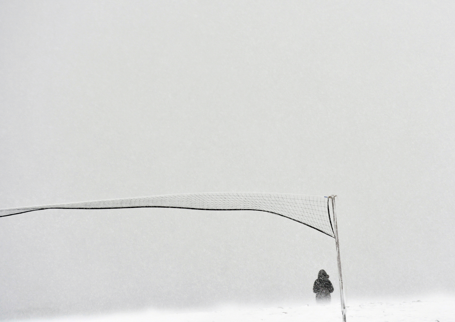 Nikon D500, 1/320 @ f/5.6, ISO 250, 70-200mm  A person walks along Devereaux in Marblehead in whiteout conditions during Winter Storm Stella.