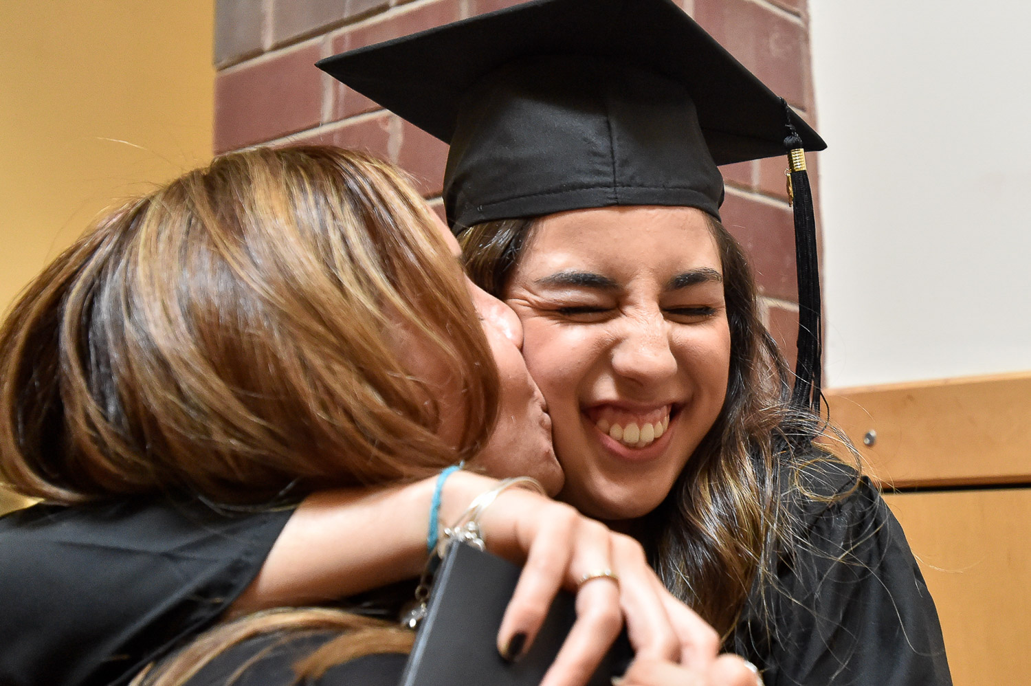 Nikon D4s, 1/320 @ f/4.0, ISO 8,000, 17-35mm  Victoria Brochetto gets a kiss from her mother Patricia at the conclusion of the Ipswich High School Class of 2017 Graduation inside the school gymnasium, Sunday, June 4, 2017. [Wicked Local Staff Photo / David Sokol]