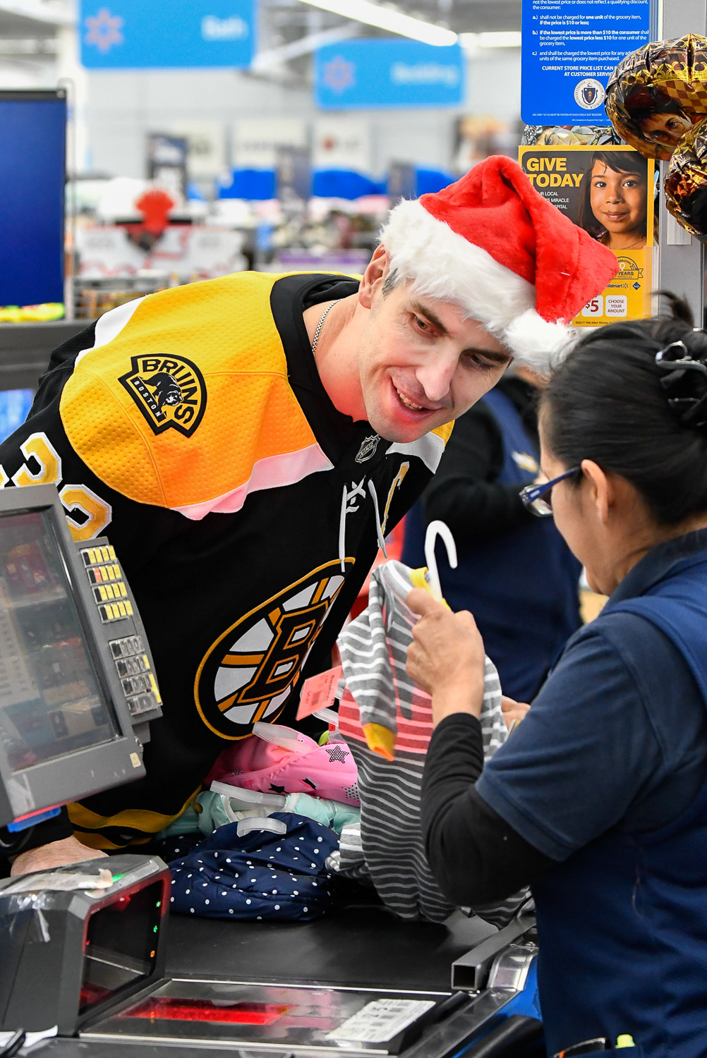 Nikon D500, 1/250 @ f/4, ISO 3200, 70-200mm  Zdeno Chara, Boston Bruins defenseman, peaks at the cashiers register screen as he checks out after shopping at Walmart in Saugus during the Bruins Annual Holiday Toy Shopping event where gifts purchased by members of the Boston Bruins will be donated to area hospitals around Boston for children who are unable to celebrate the holidays at home, Thursday, Nov. 30, 2017. [Wicked Local Staff Photo / David Sokol]