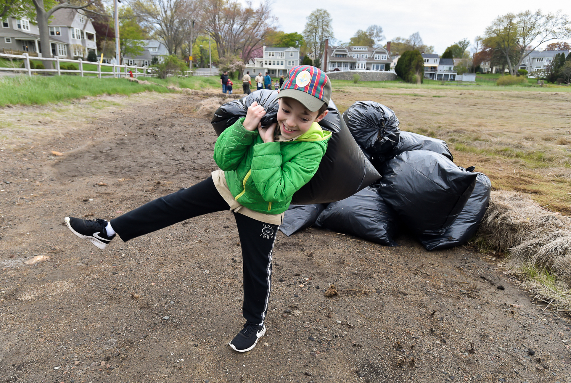 """Nicholas Dube, 9, of Cub Scout Pack 11, carries a trash bag full of old marsh debris known as """"marsh vomit"""" while cleaning up the marsh around Goldthwait Reservation, Tuesday evening, May 9, 2017. [Wicked Local Staff Photo / David Sokol]"""