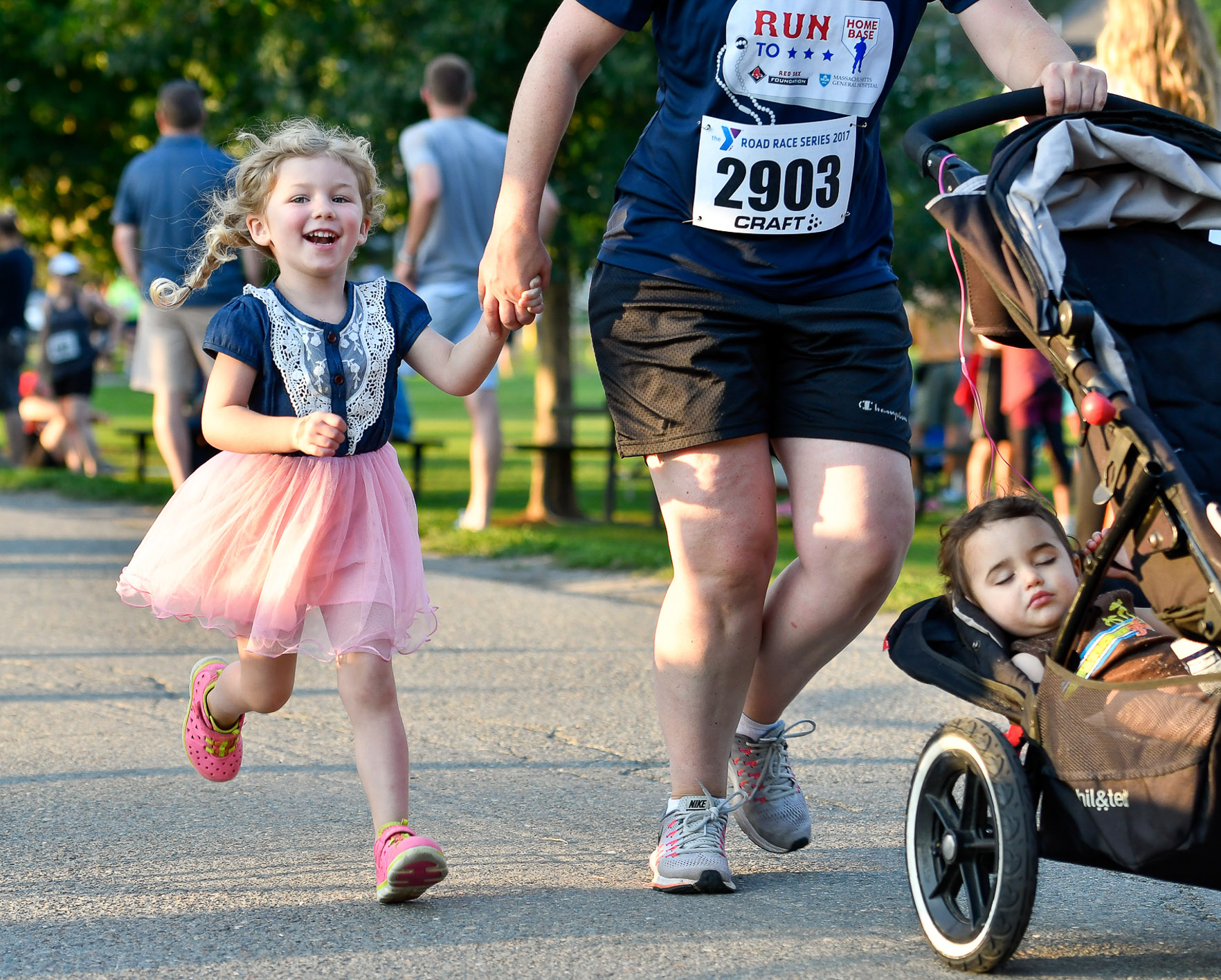 Jessica Cargile holds her daughter Zoey's, 3, hand while she pushes a carriage with her sleeping son Liam, 1, towards the finish line during the 50th Annual Beverly Yankee 5K Road Race at Lynch Park, Thursday, Aug. 3, 2017. [Wicked Local Staff Photo / David Sokol]