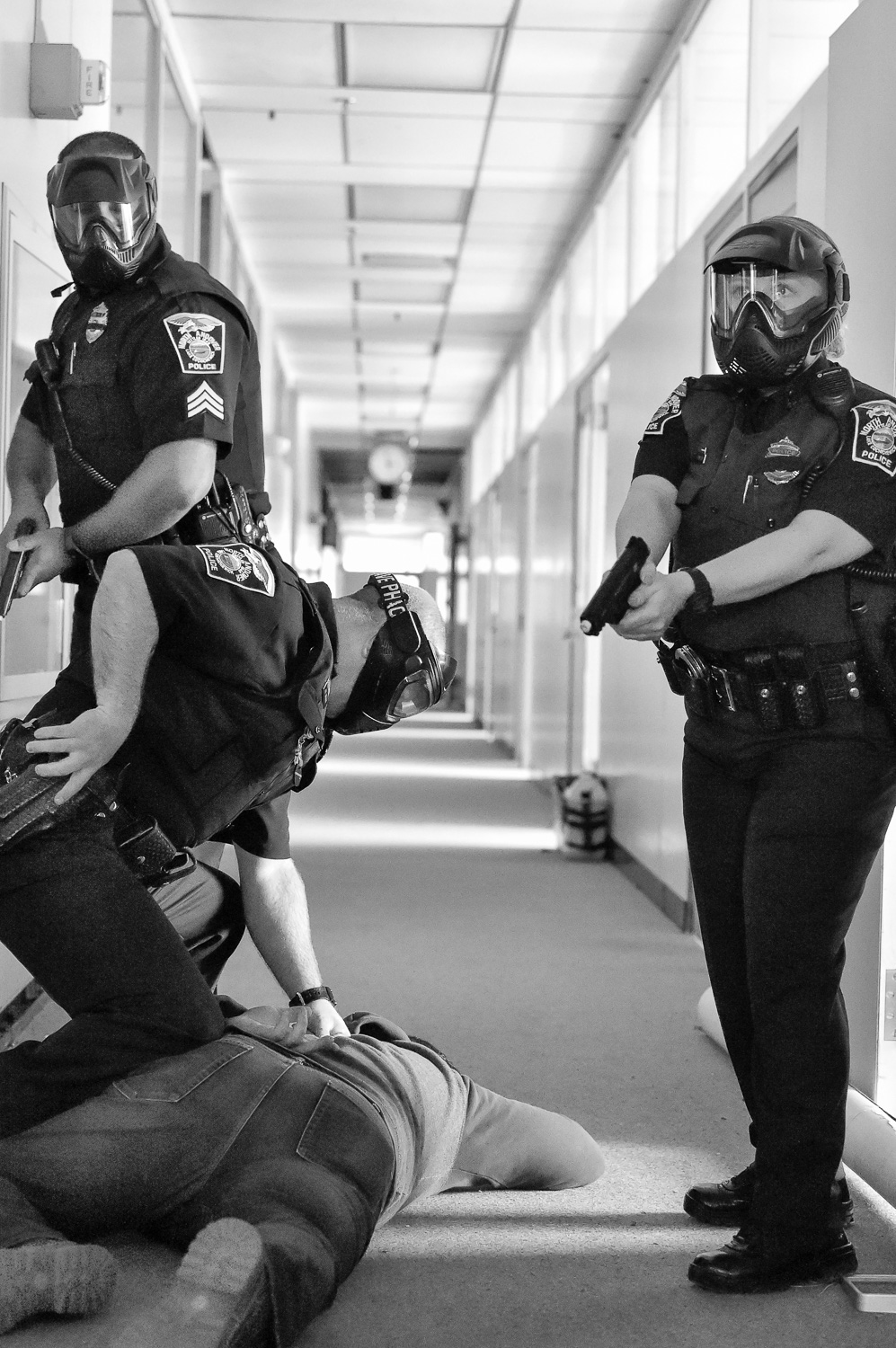 Nikon D4s, 1/1,000 @ f/4, ISO 18,000  North Andover police officer Jason Wedge checks on a victim as Sergeant Fredy Almanzar and officer Ashley Kneeland provide coverage during an active shooter training at Osgood Landing on Wednesday, April 18, 2018. [Wicked Local Staff Photo / David Sokol]