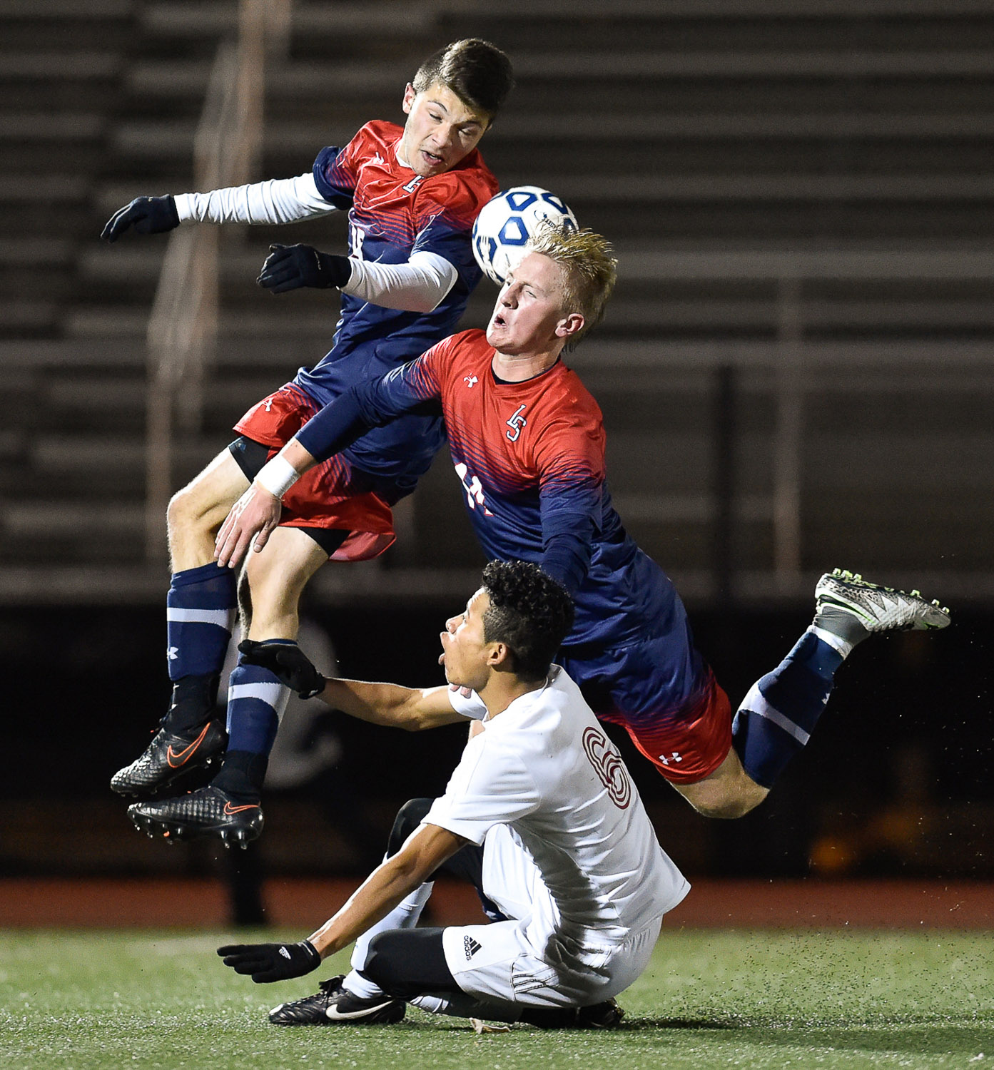 Nikon D4s, 1/1600 @ f/2.8, ISO 6400, 300mm  Lincoln-Sudbury's Andre Kotikian and Landon DeCesare-Fousek get tripped up by Somerville's Edwin Mejia Sanchez as they battle for a loose ball during their north division 1 game at Manning Field in Lynn, Wednesday, Nov. 9, 2016. [Wicked Local Photo by David Sokol]