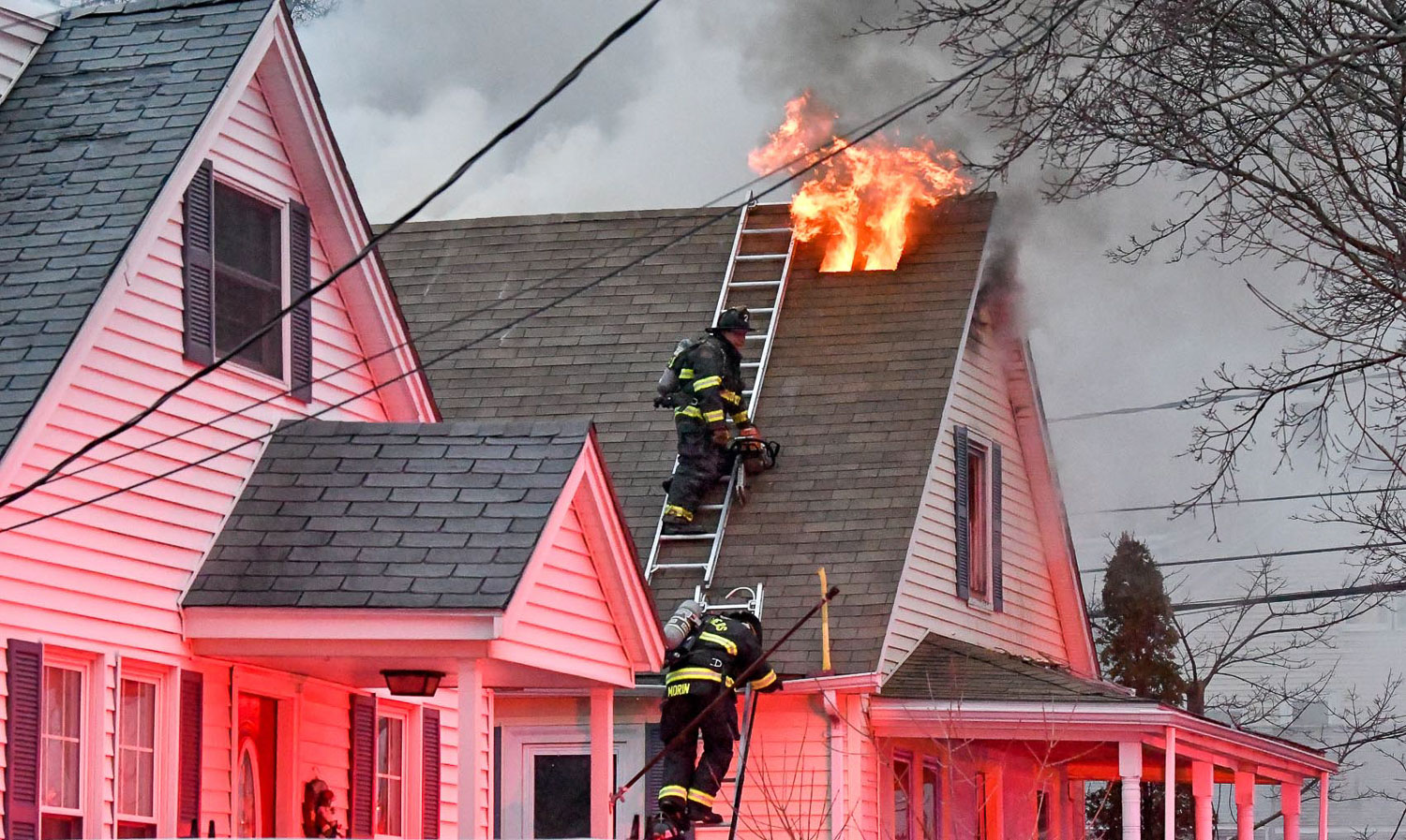Second Place Spot News:  Danvers firefighters retreat down a ladder after venting the roof while fighting a two alarm fire at 71 Poplar Street shortly before 7 p.m. on Tuesday, April 3, 2018. [Wicked Local Staff Photo / David Sokol]