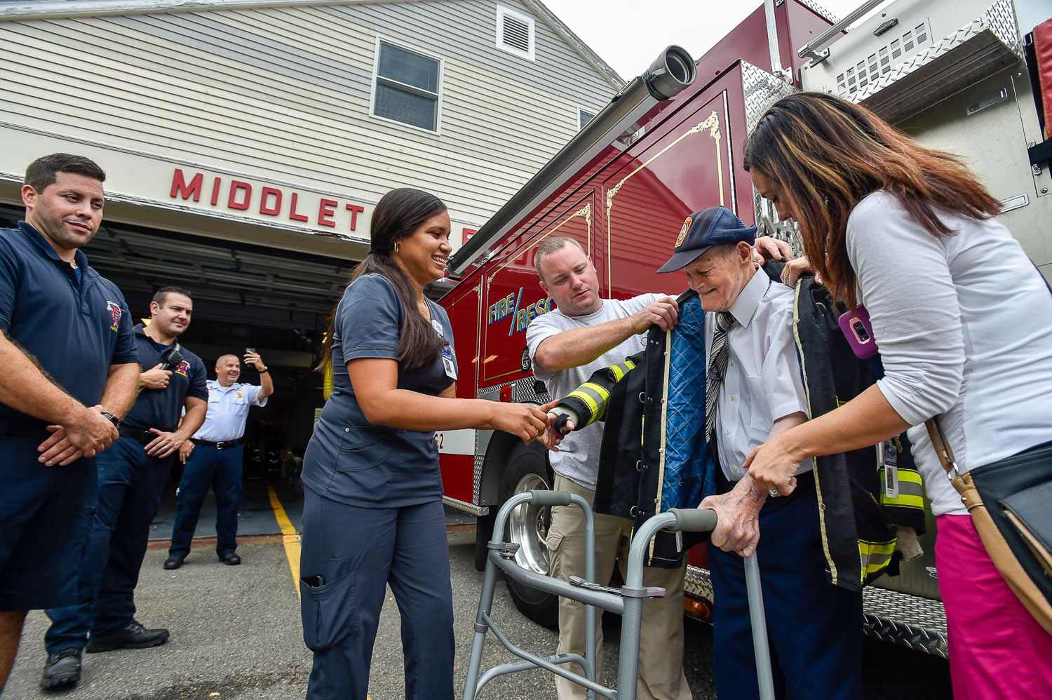 5 of 9 Honorary Middleton firefighter Bobby Jensen, center, receives help putting on a firefighters jacket from Lismery Ortiz, Hospice Aide at Compassus, Captain Doug LeColst, and Maureen Brancato, Hospice Nurse at Compassus, during his visit to the Middleton Fire Department, Thursday, Sept. 14, 2017. [Wicked Local Photo / David Sokol]