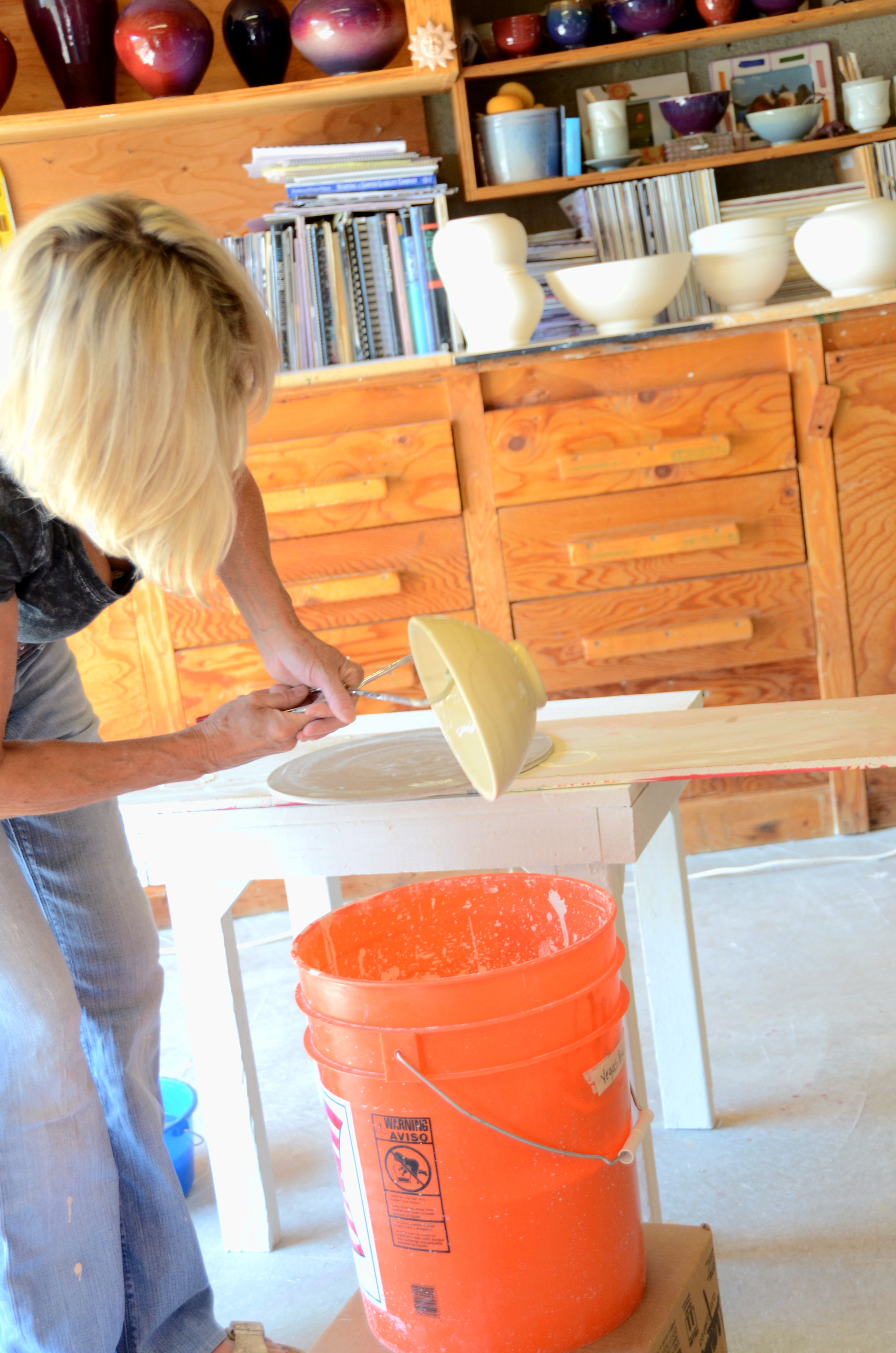 Shelly Caldwell hand glazing their porcelain pieces in their Park City studio.  Preparing for a cone 10 firing | Caldwell Pottery